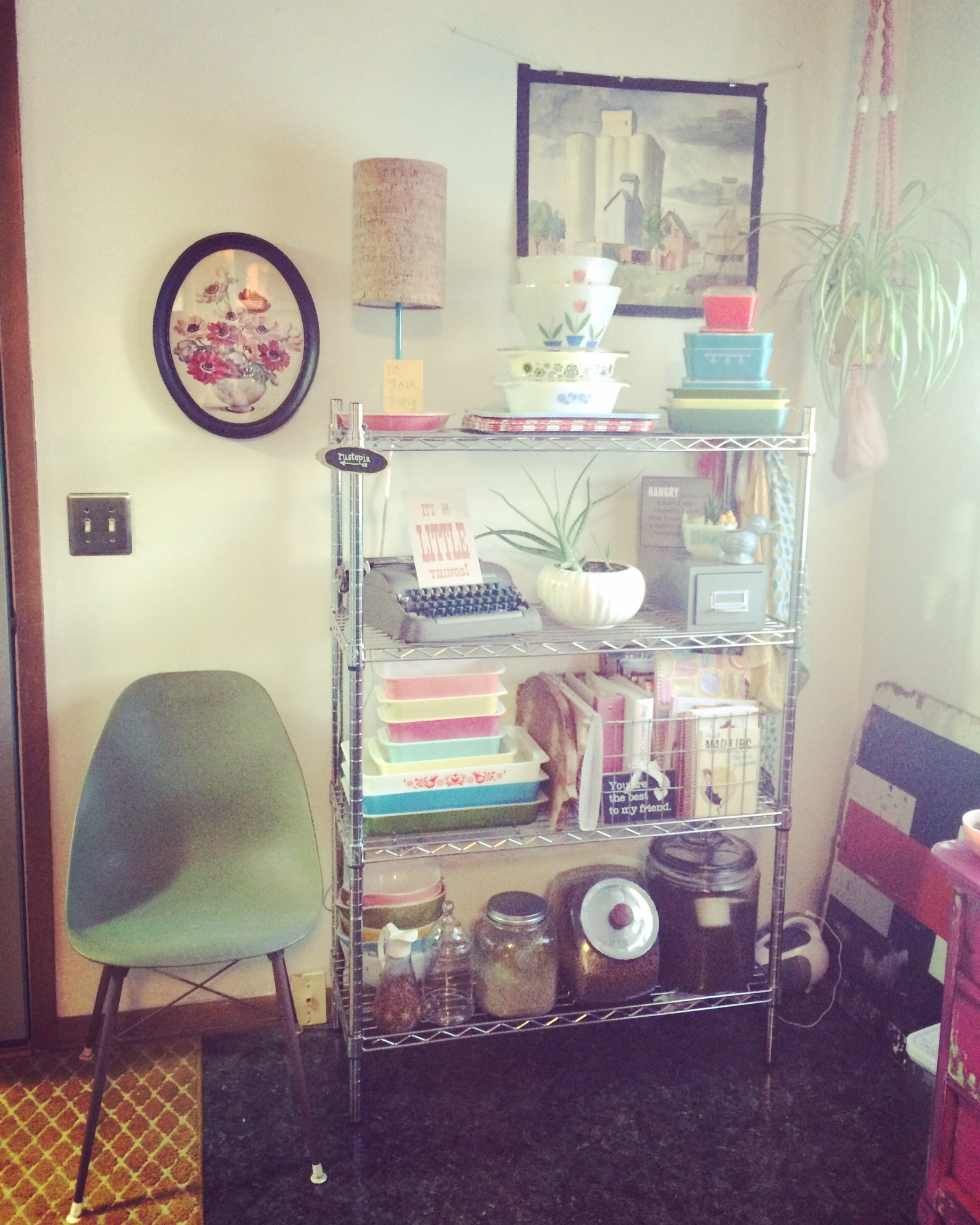 Vintage chair next to a metal shelving unit decorated with colorful vintage dishes.    RustopiaConsulting.com