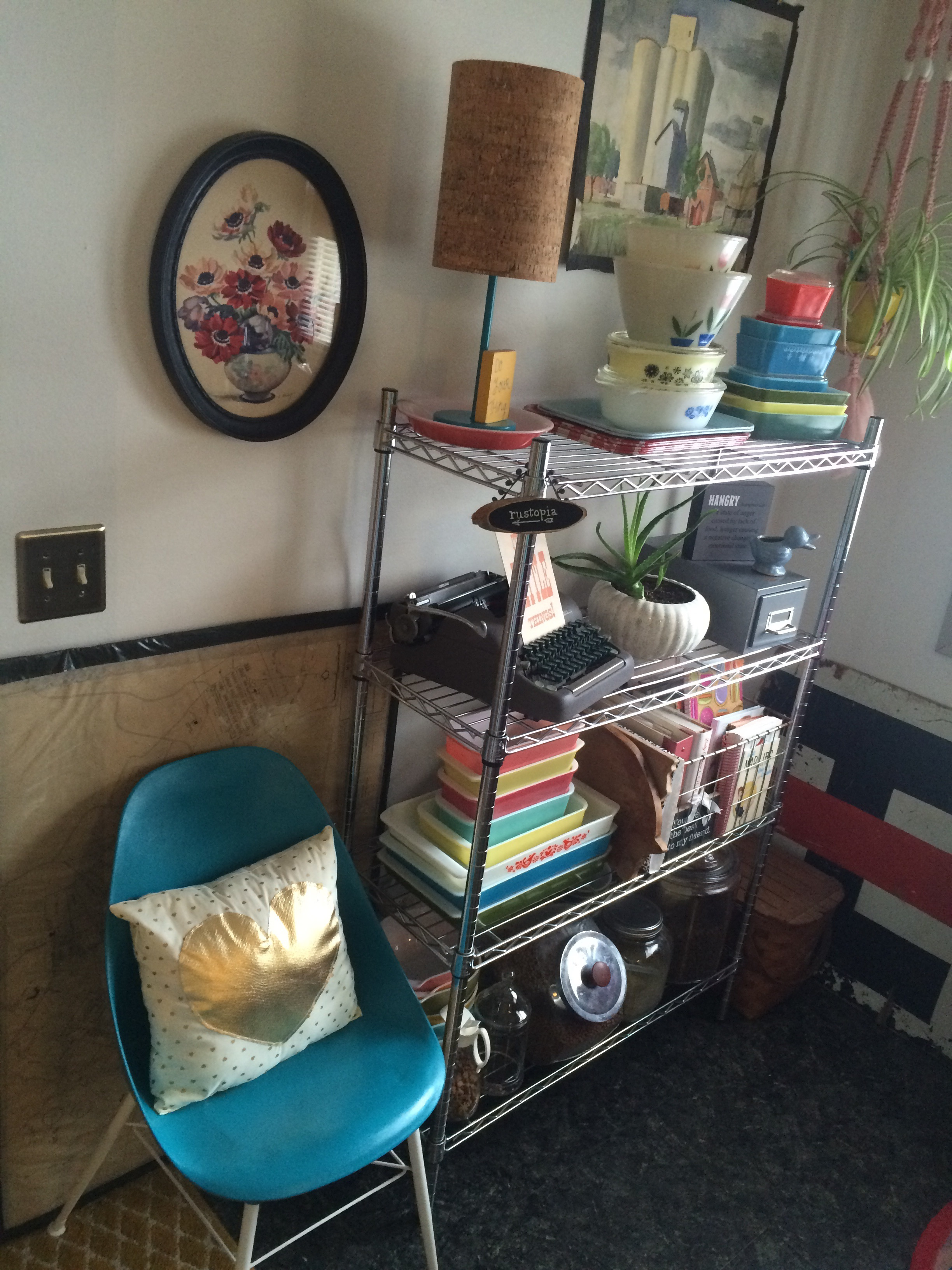 Teal vintage chair with white and gold pillow next to metal shelving with color dishes.    RustopiaConsulting.com