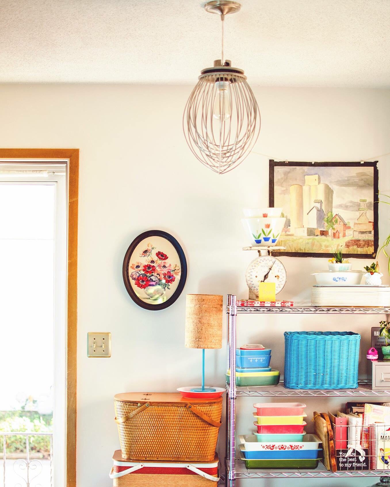 Mixer whip light fixture above a metal shelf decorated with colorful vintage dishes. || RustopiaConsulting.com