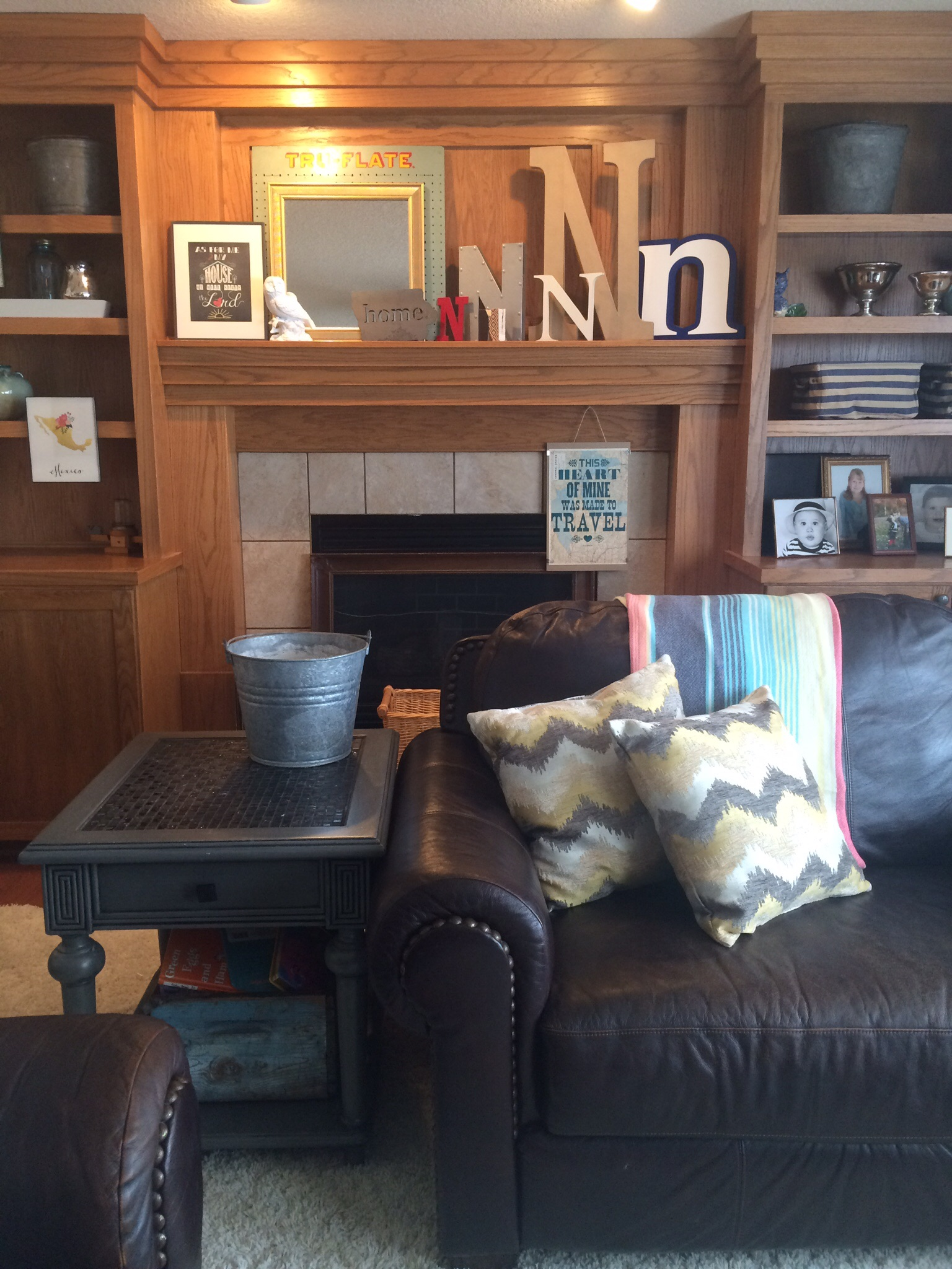 A mantel decorated with several letter N's behind a couch and end table. || RustopiaConsulting.com