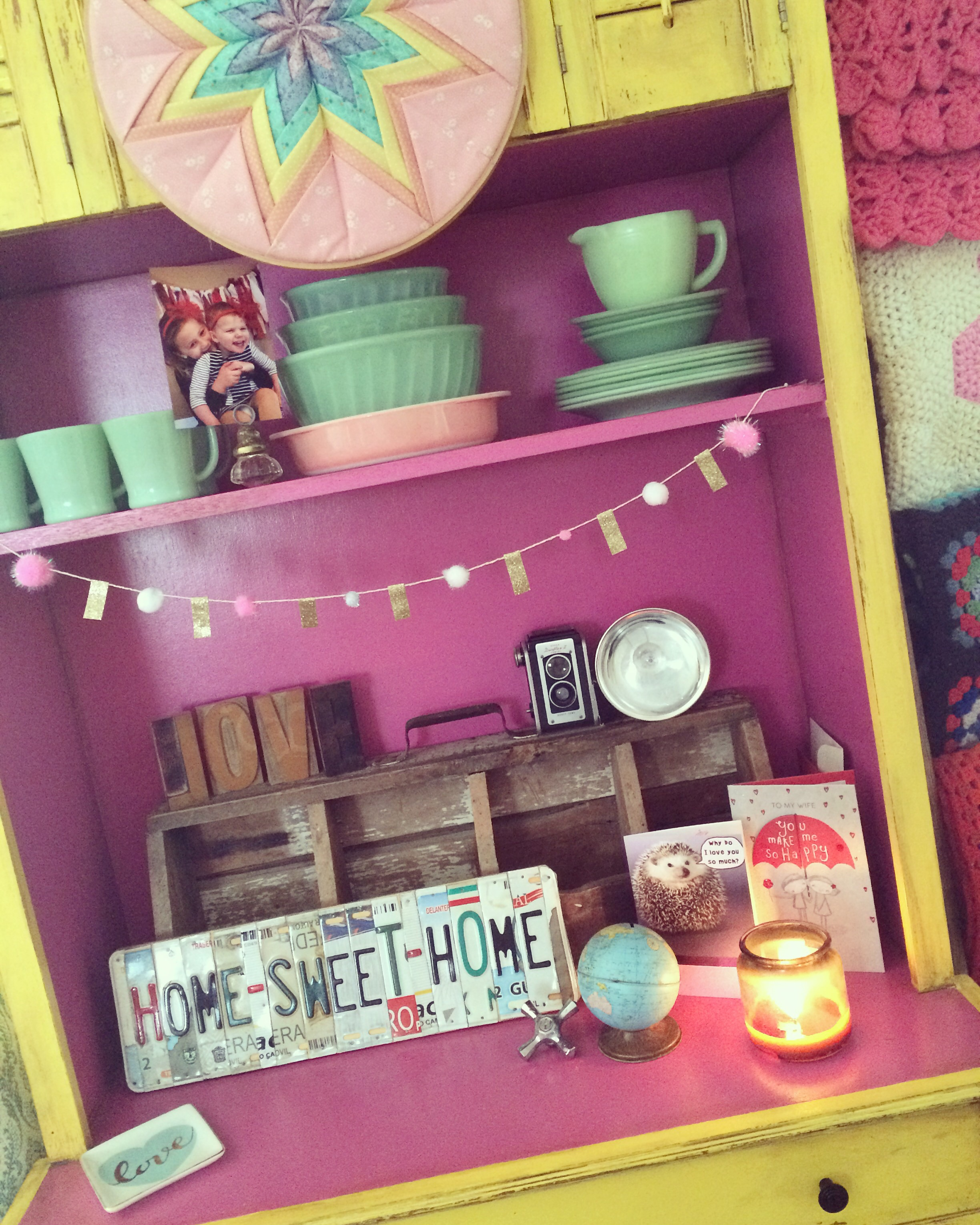 """Pink and yellow hutch decorated with vintage dishes, a license plate sign that says """"home sweet home"""", and other vintage pieces. 