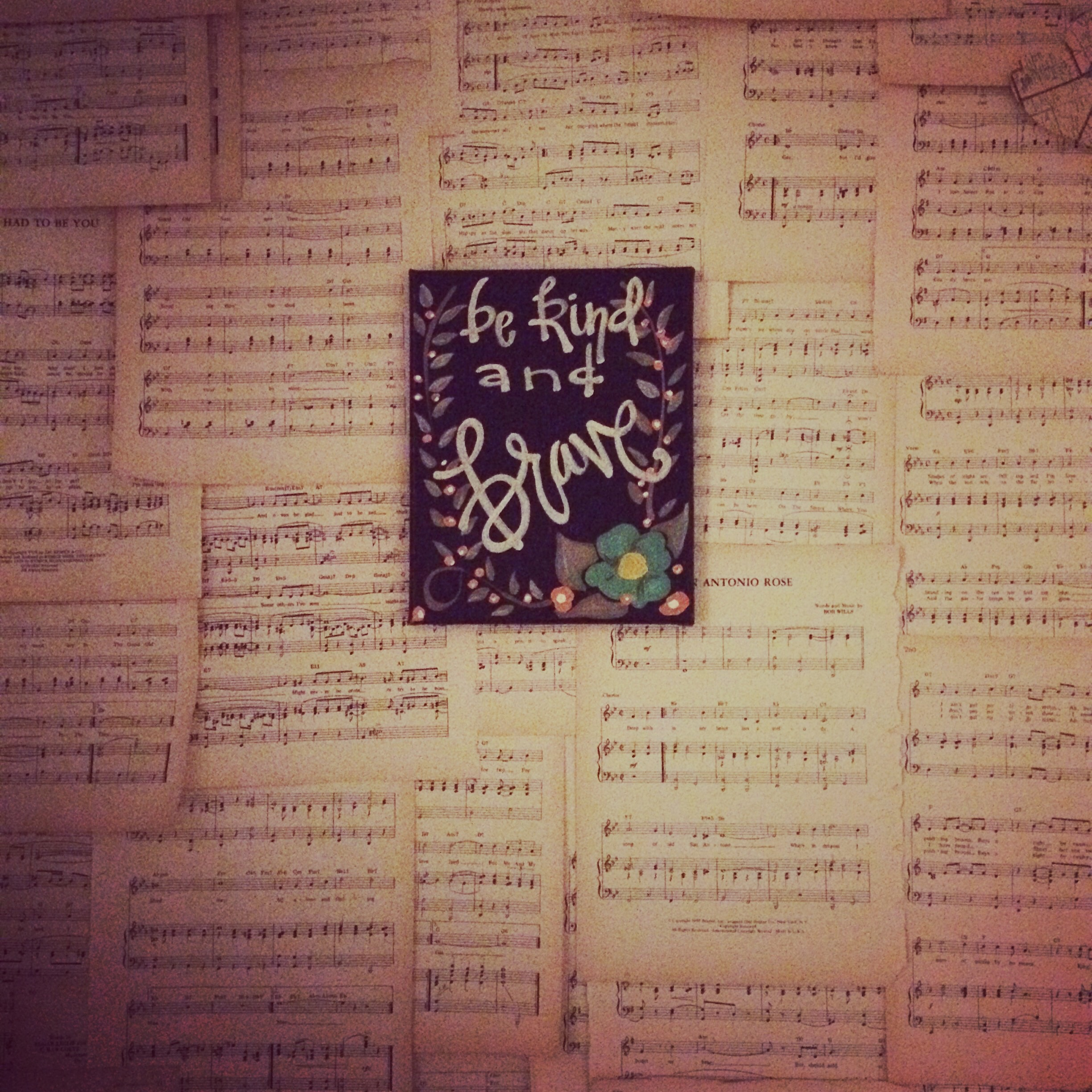 Vintage sheet music as a wall covering with a be kind and brave sign hanging. || RustopiaConsulting.com