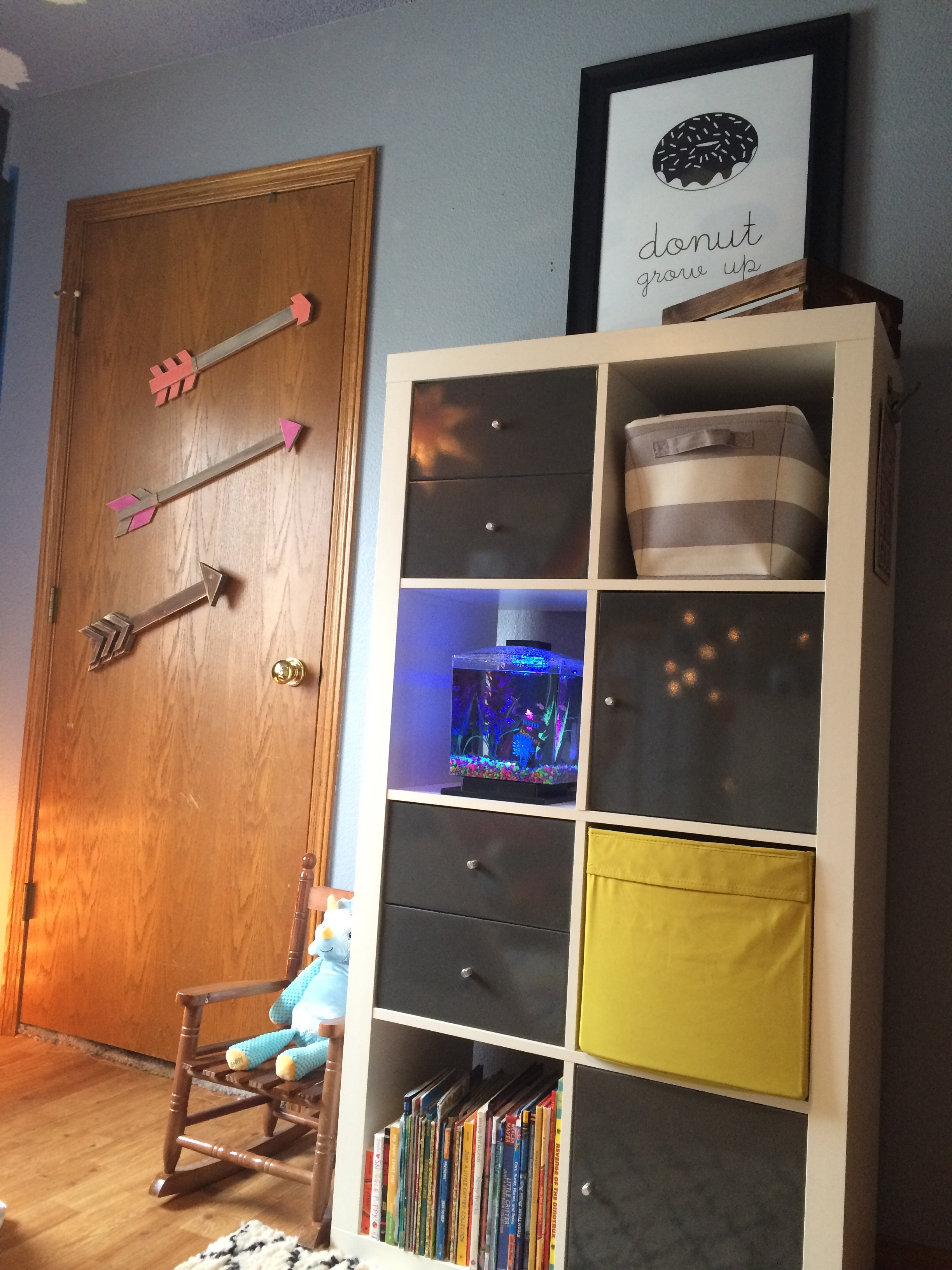 Cubby organizer with gray and yellow bins, kids books, and a fish tank. || RustopiaConsulting.com