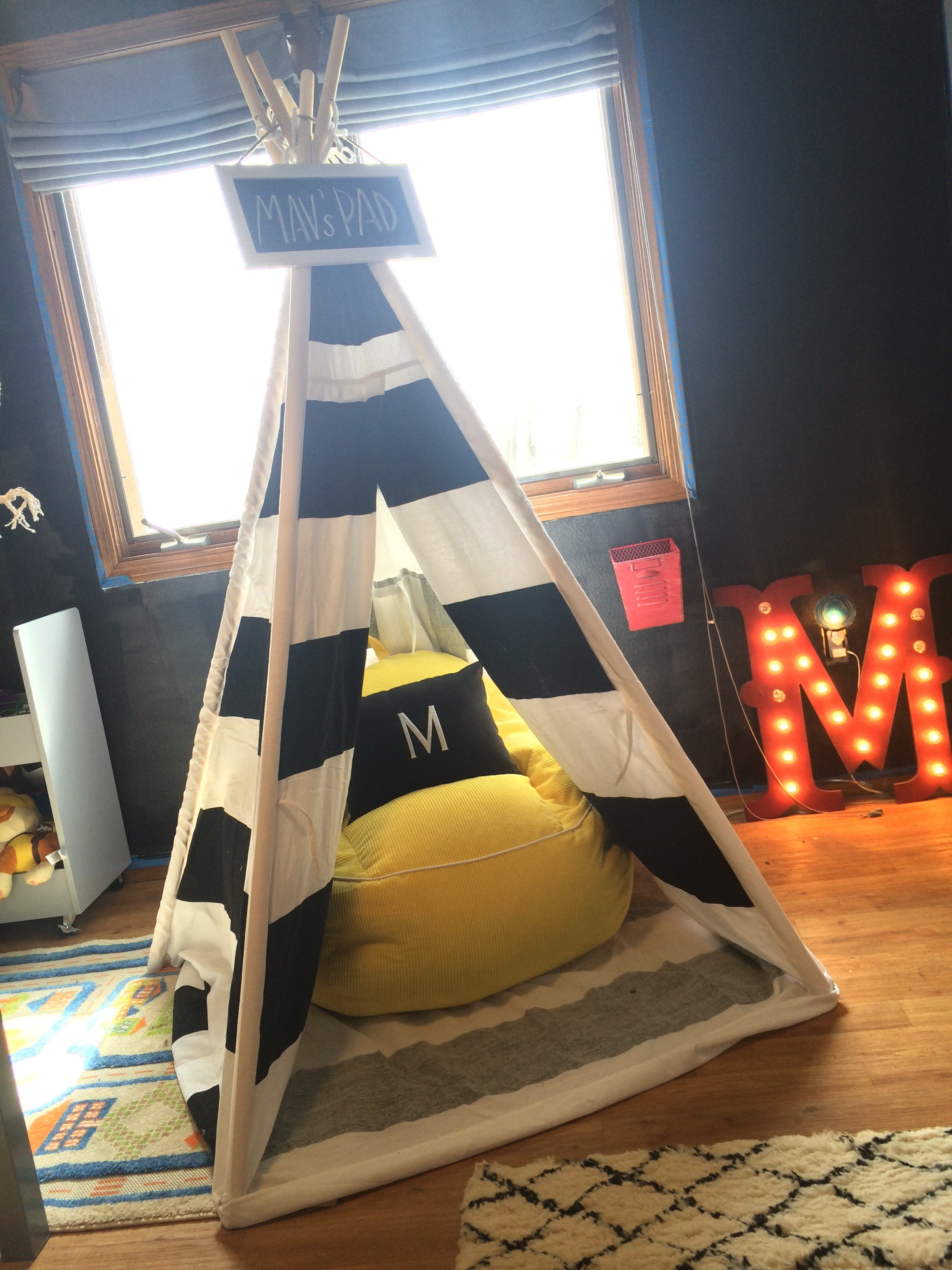 Striped teepee tent with a yellow beanbag chair inside. || RustopiaConsulting.com