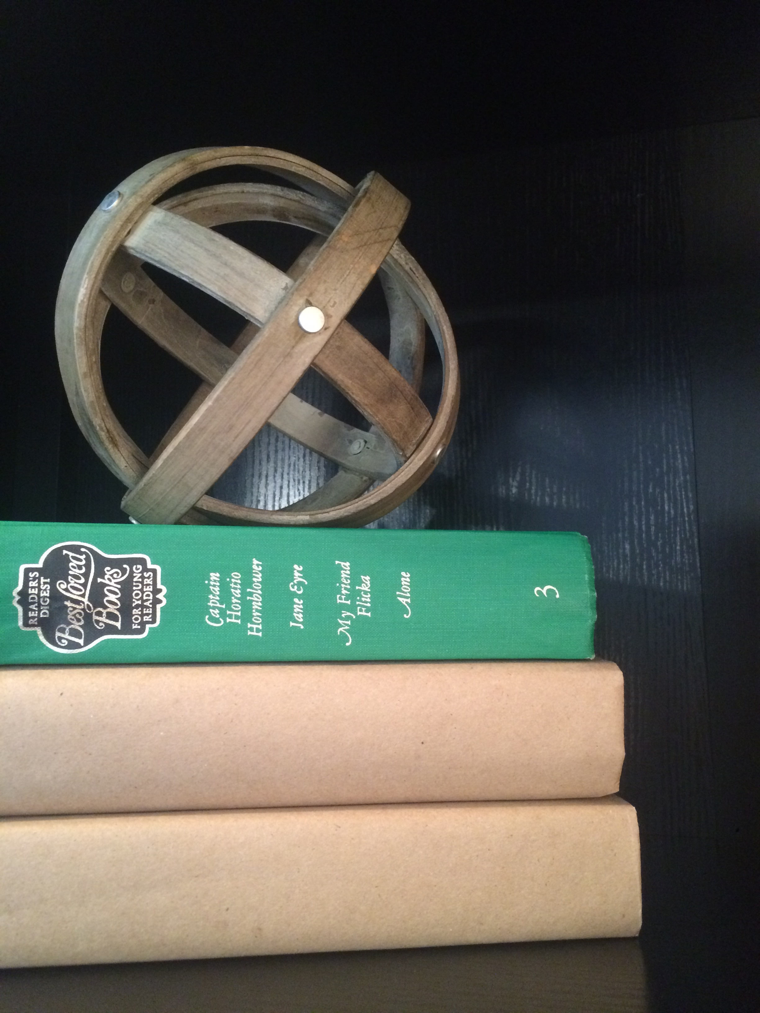Wooden orb on a stack of tan and green books as home decor. || RustopiaConsulting.com