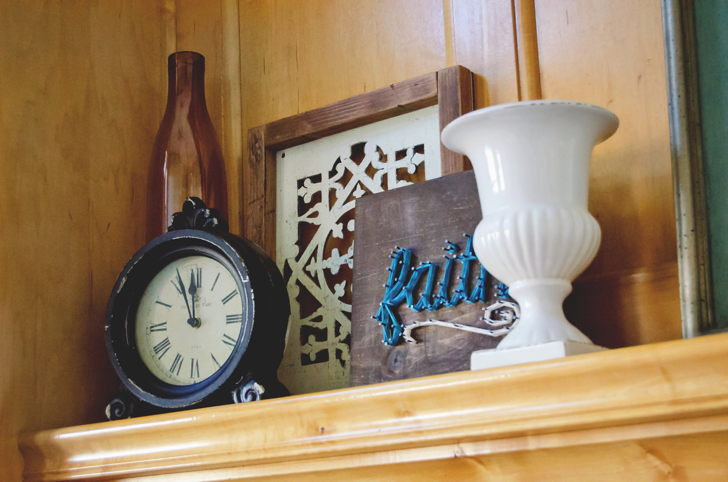 Mantel vignette with a vintage clock, white vase, and a string art sign. | hprallandco.com