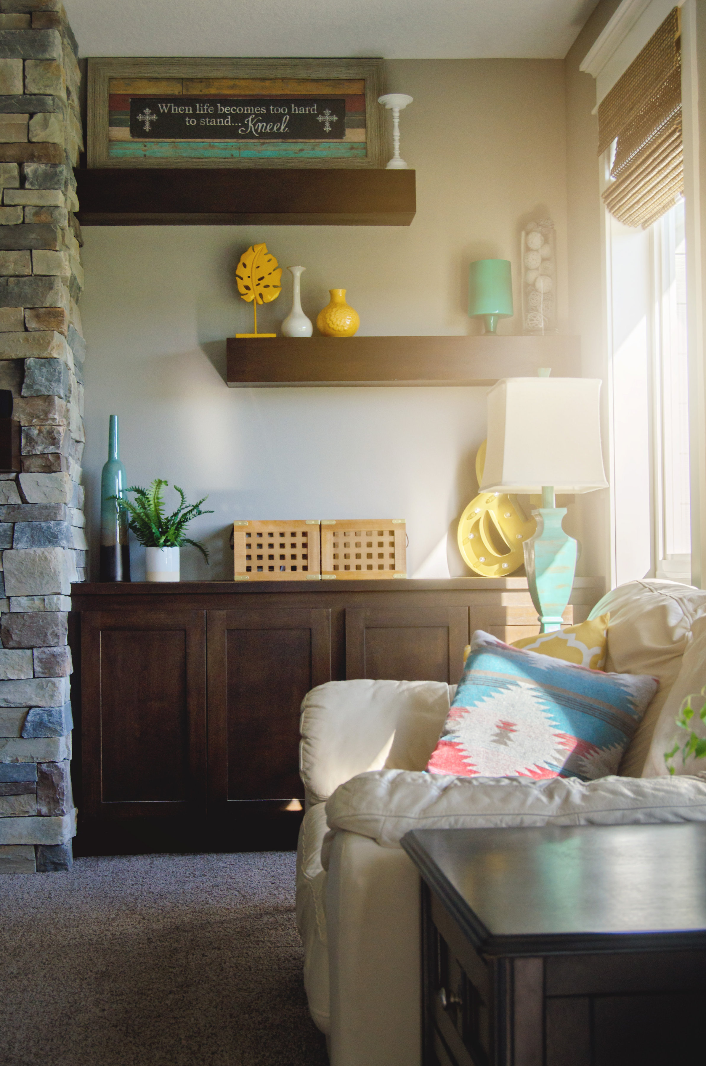 Living room shelves decorated with pops of yellow and aqua. | hprallandco.com