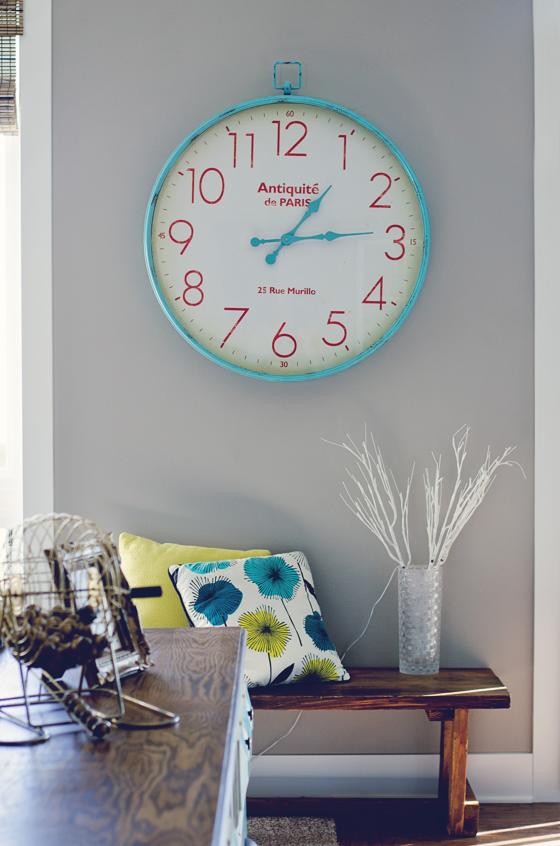 Aqua and red wall clock over a sweet wooden bench. || RustopiaConsulting.com