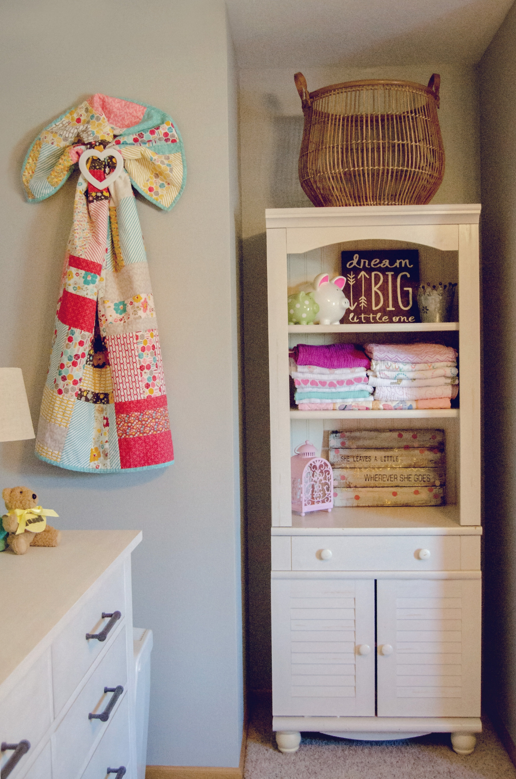 White hutch as nursery storage with a colorful quilt wall hanging. | hprallandco.com