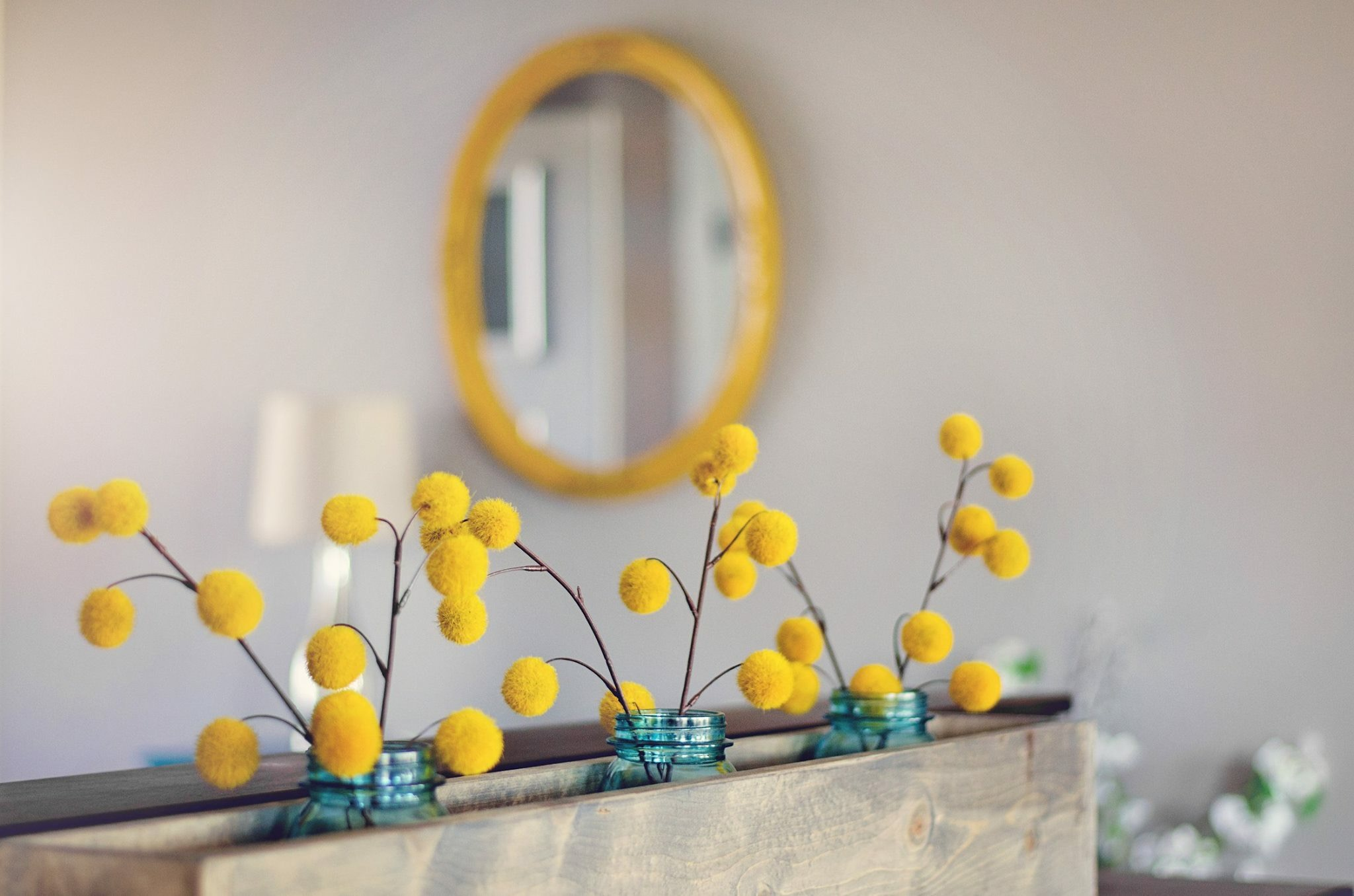 Yellow billy buttons in aqua ball jars with a yellow framed circular mirror in the background. RustopiaConsulting.com