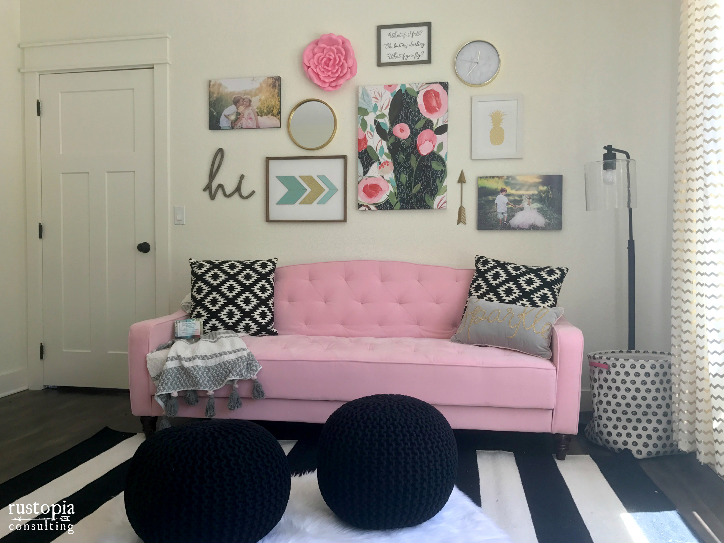 Home office with a pink couch, a gallery wall, and black floor poufs by RustopiaConsulting.com