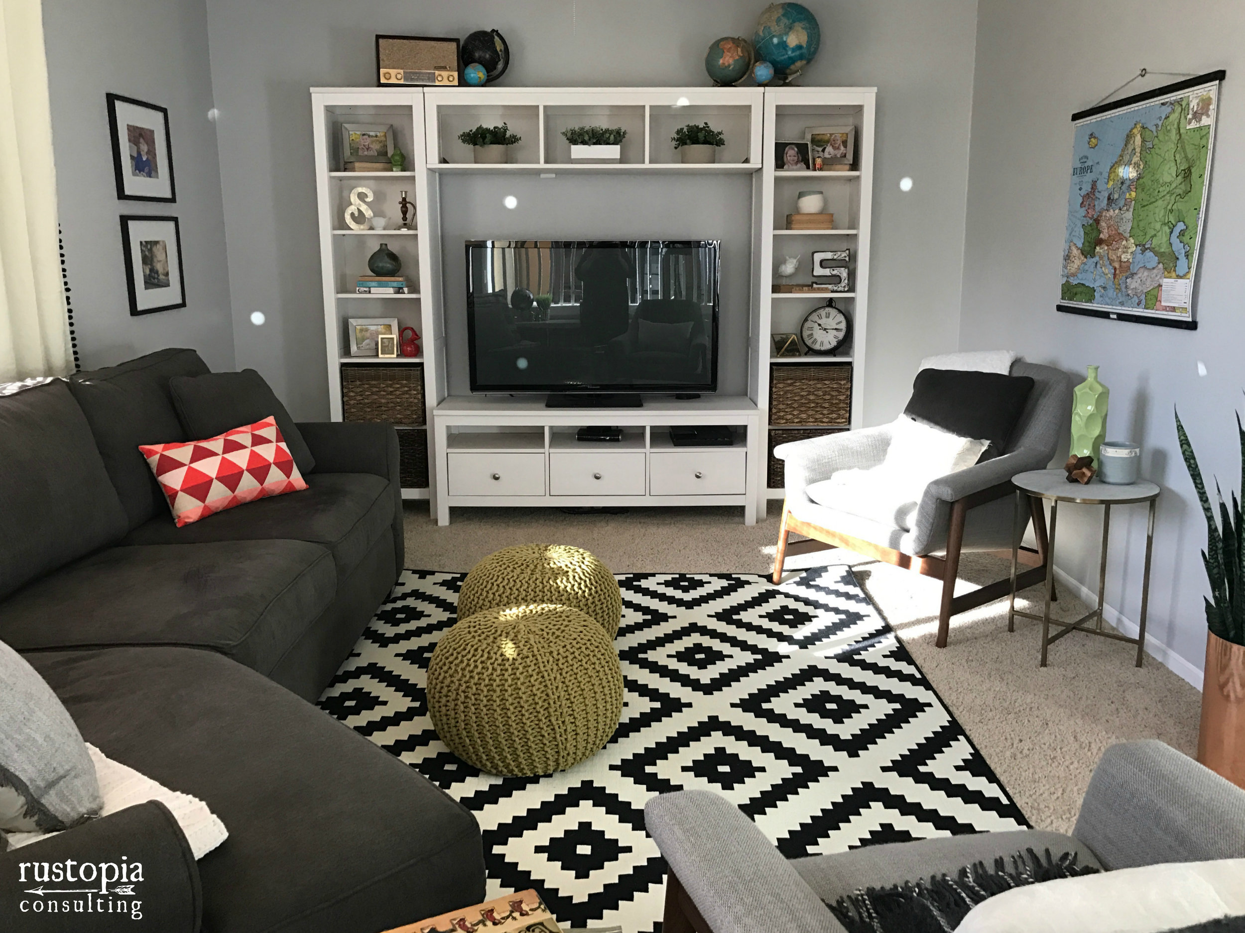 Living room design with a black and white area rug, and sage green floor poufs by RustopiaConsulting.com