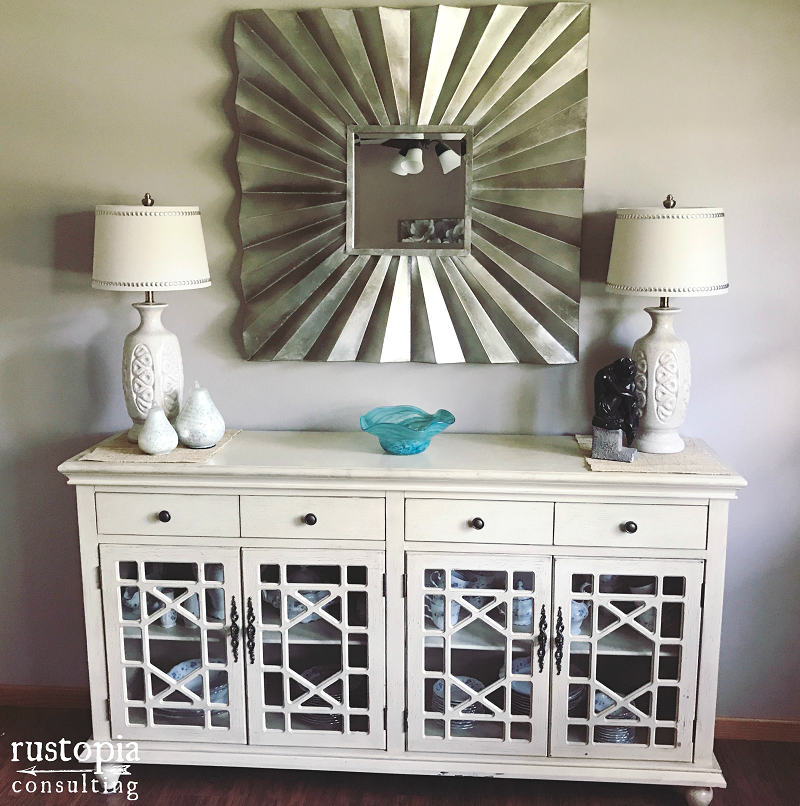Cream colored buffet with matching lamps, and a large square mirror. | RustopiaConsulting.com