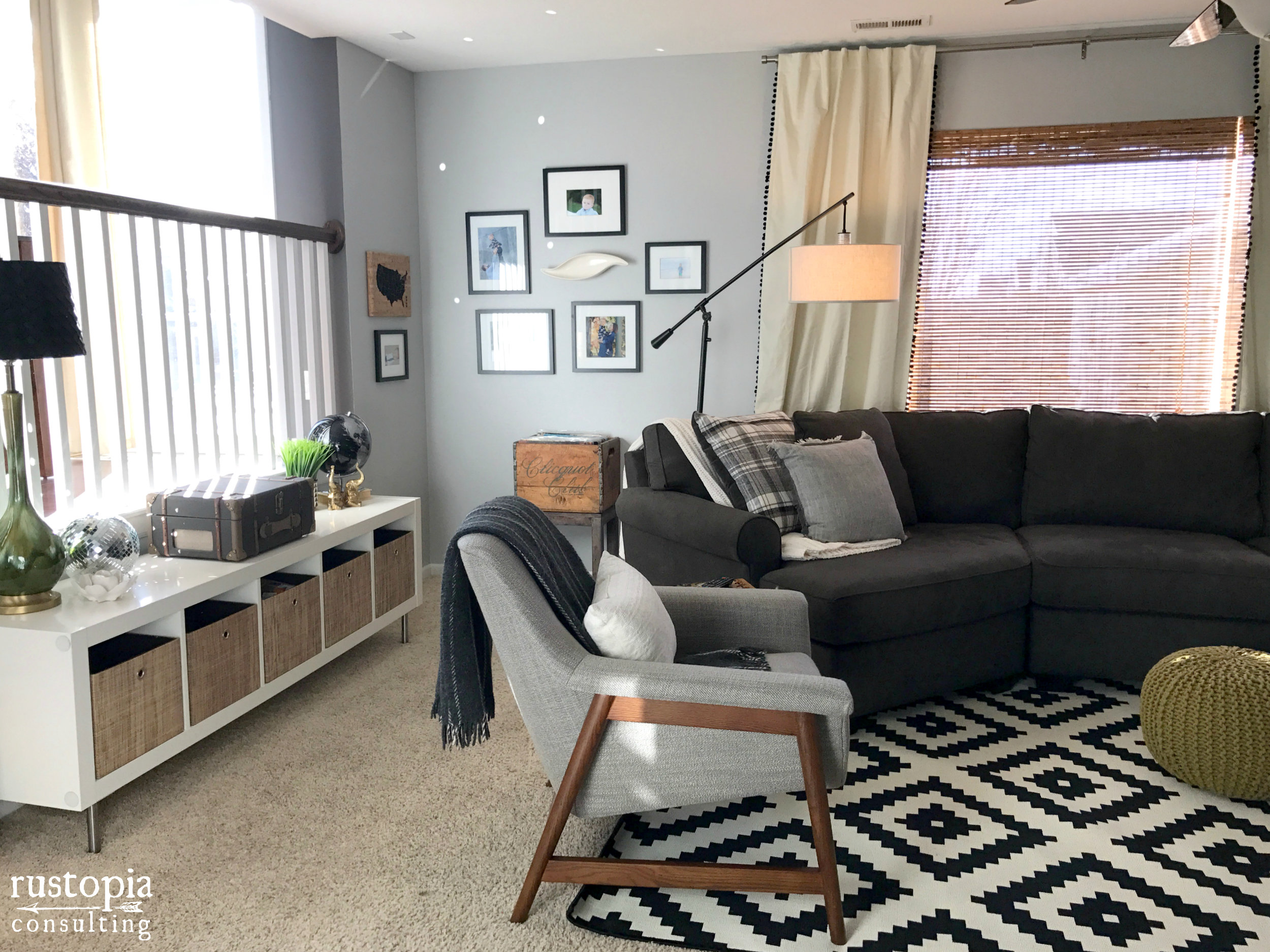Living room design with a black and white area rug, floor lamp, and a gray accent chair. | RustopiaConsulting.com