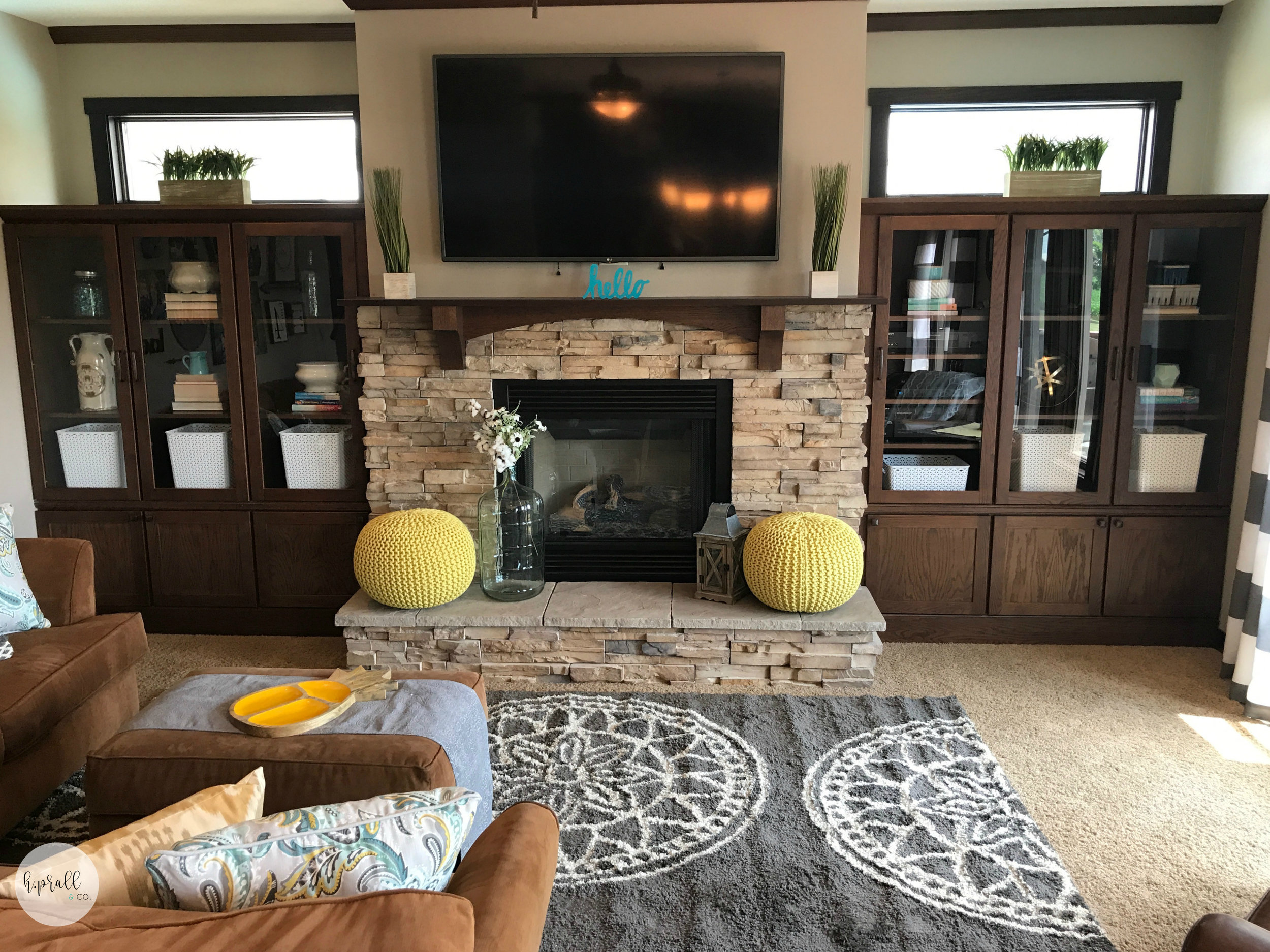 Living room design with yellow poofs, and a gray area rug from  H.Prall and Co.