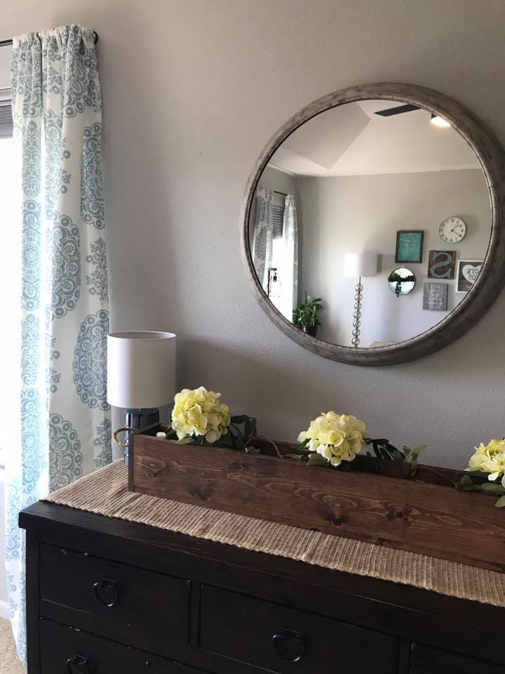 Round mirror hanging above a dresser in a mater bedroom via  H.Prall & CO.
