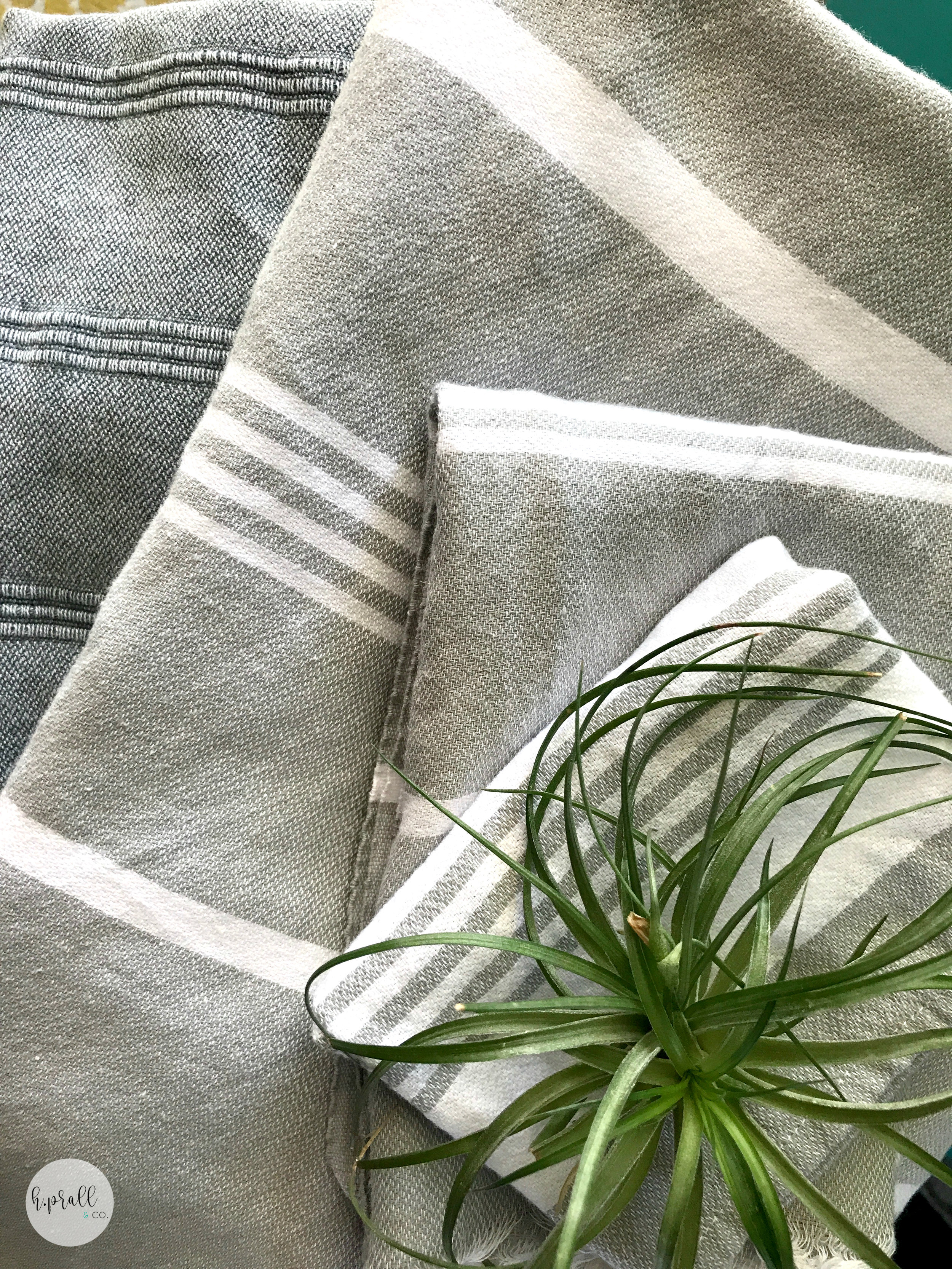 Gray and white striped Turkish towels with a succulent plant sitting on top via  H.Prall & Co.
