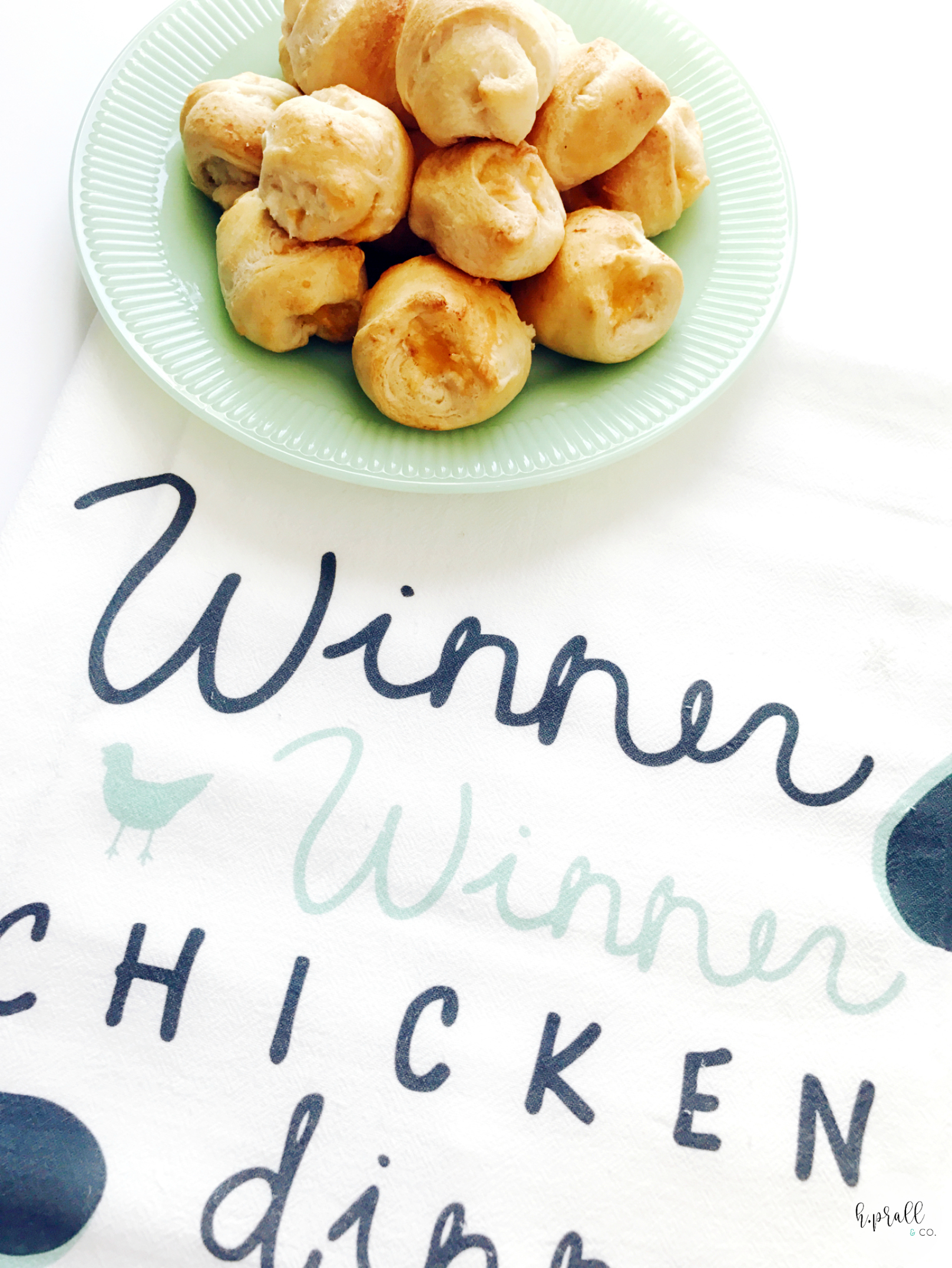 """Plate of Chicken Puffs sitting on a """"Winner Winner Chicken Dinner"""" tea towel.   H.Prall & Co."""