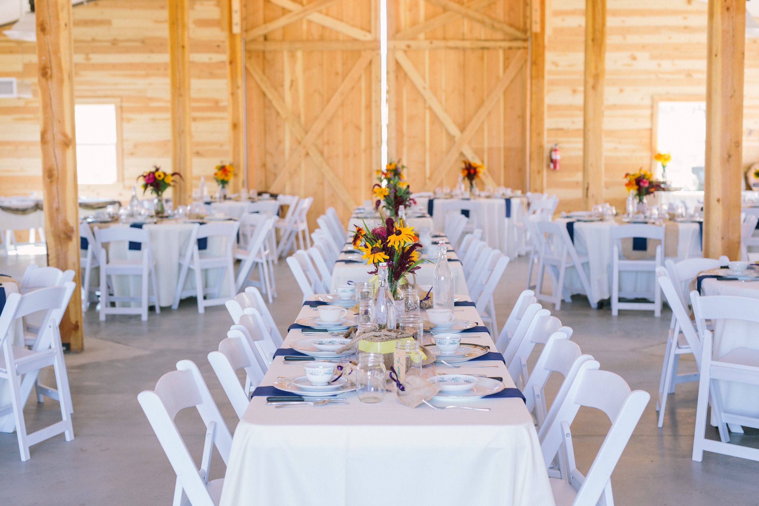 Farm-fresh flowers add a lovely pop of color to dinner in the barn. Photo by Dina Remi Studios.