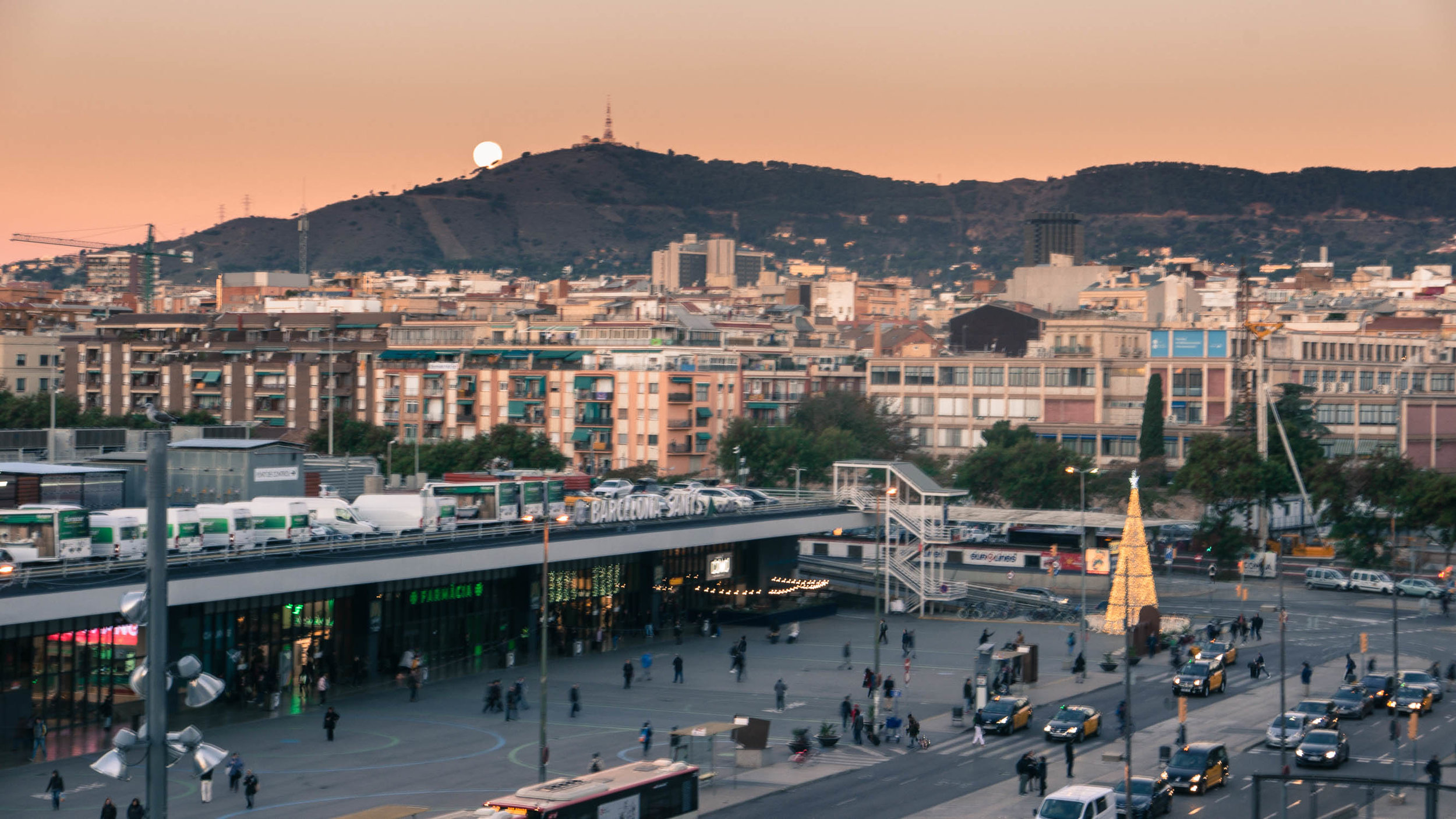 Early morning moon setting over the Barcelona Train Station in December.