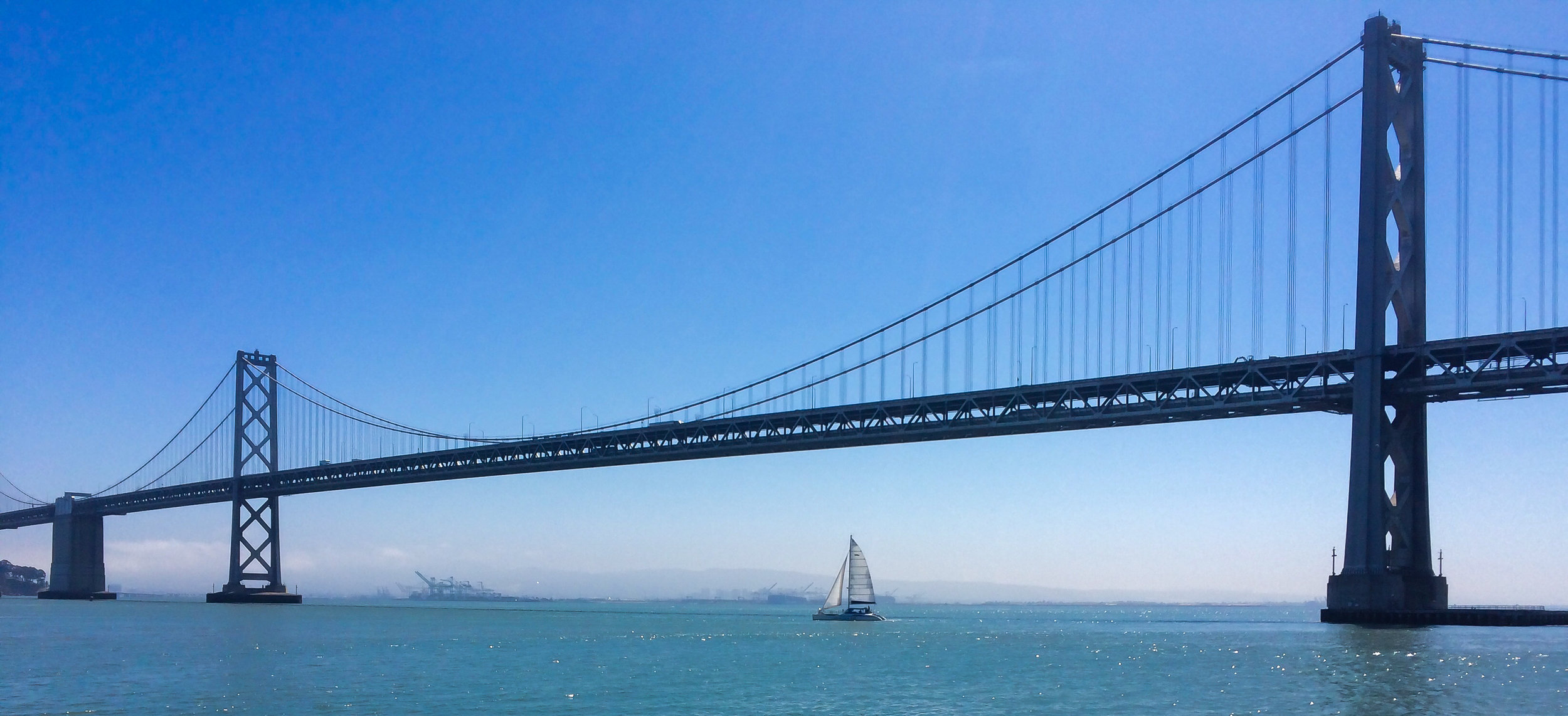 Sailboats and the Mission Trail pass under the Bay Bridge.