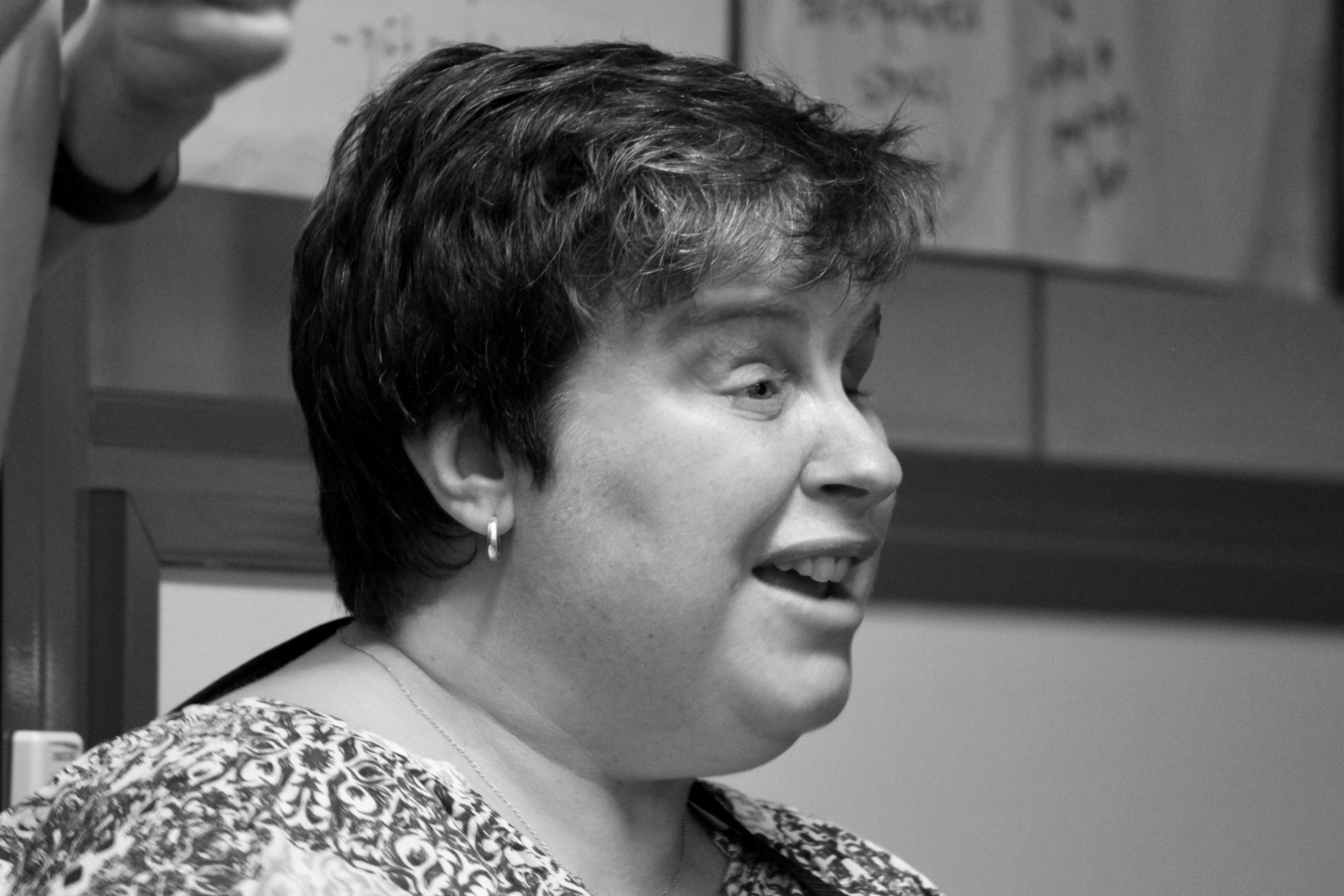 A woman is pictured, she is mid sentence, and shown on a 45 degree angle. It is a close up, she is visible from the shoulders up.