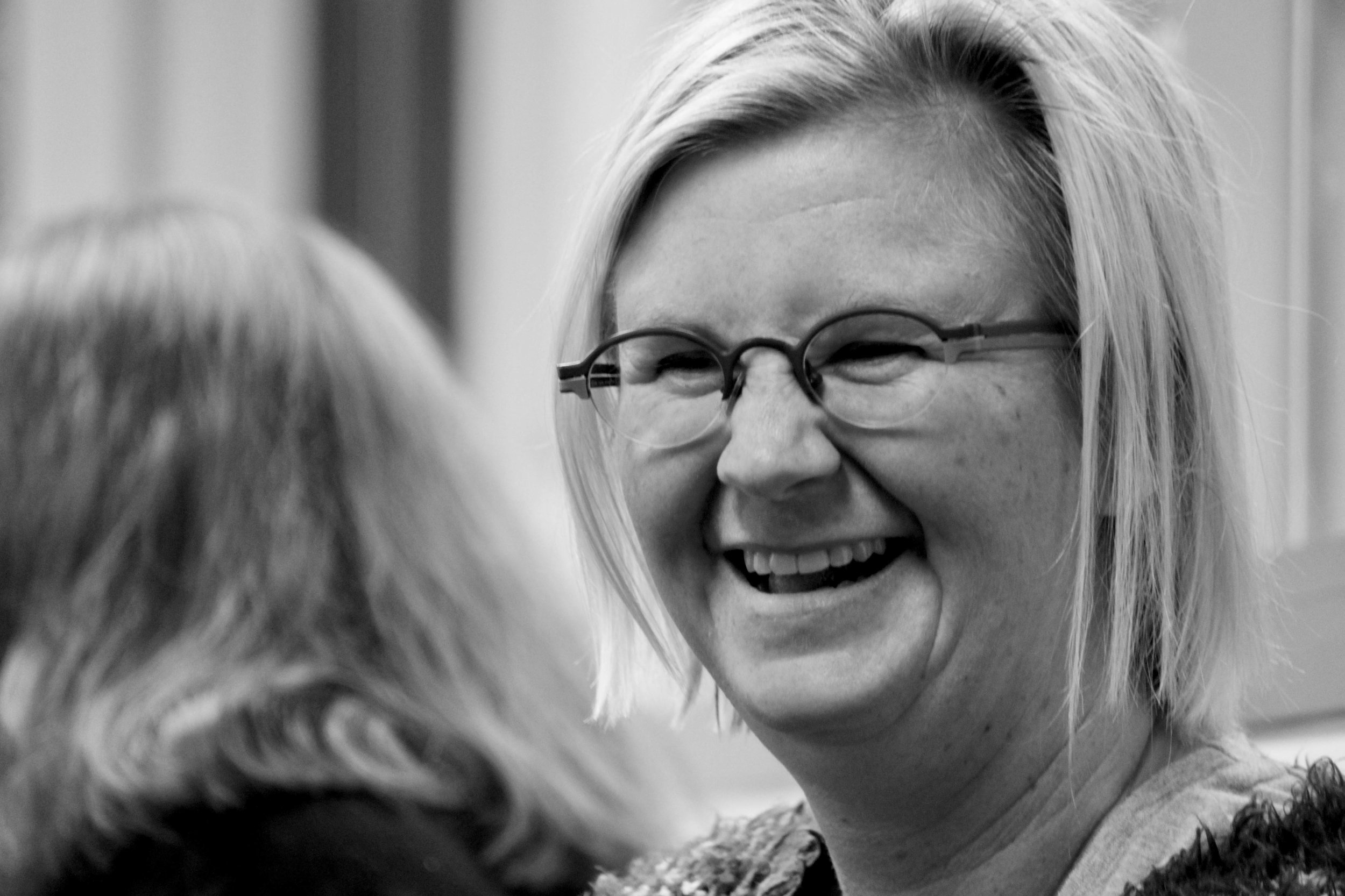 A close up of a woman's face. She wears glasses and her short hair is parted on one side. She is smiling, almost laughing at someone out of shot. It is clear she is making eye contact with the person who she is smiling at.