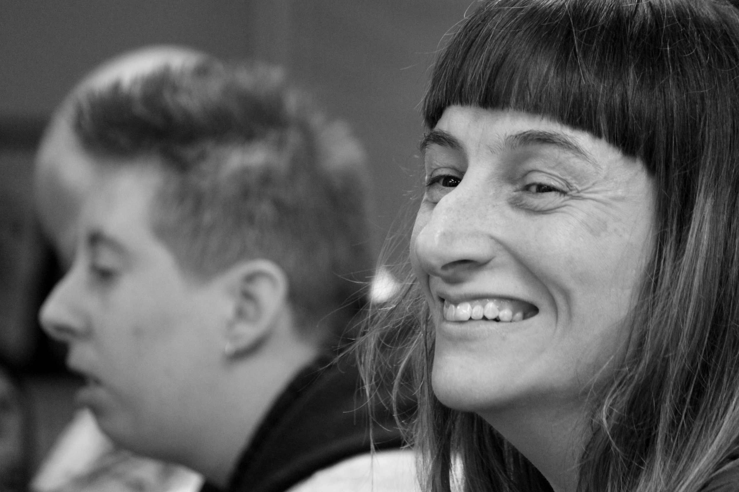 Two faces are pictured, the one out of focus is in the background on the left. The one in focus is in the foreground on the right. It is a young woman, she has a blunt fringe and a massive smile.