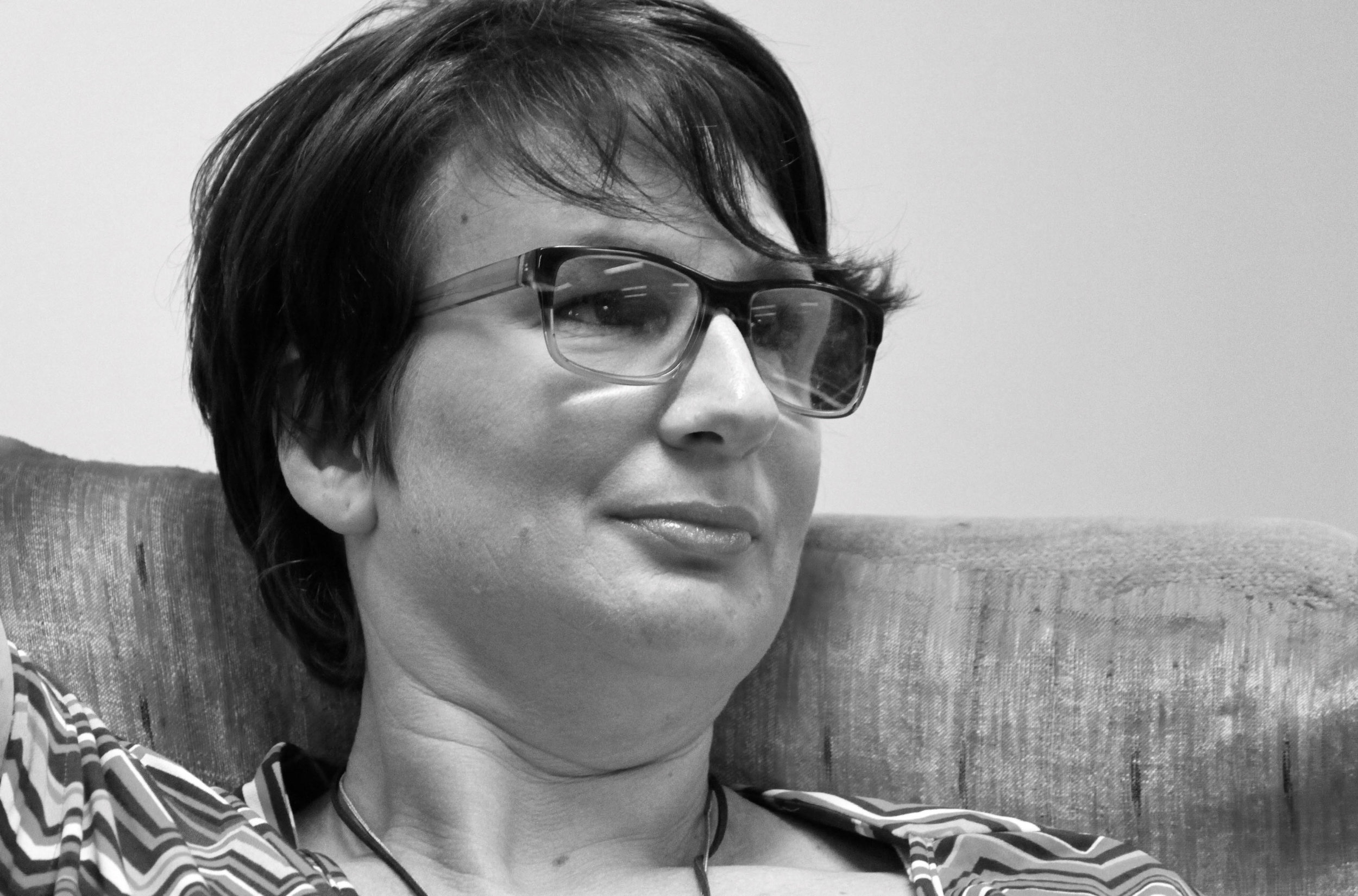 A woman's face is shown close up. She wears horn-rimmed reading glasses. Her mouth is closed not smiling, not frowning, she leans her head slightly back on a couch while she listens to a speaker out of shot.