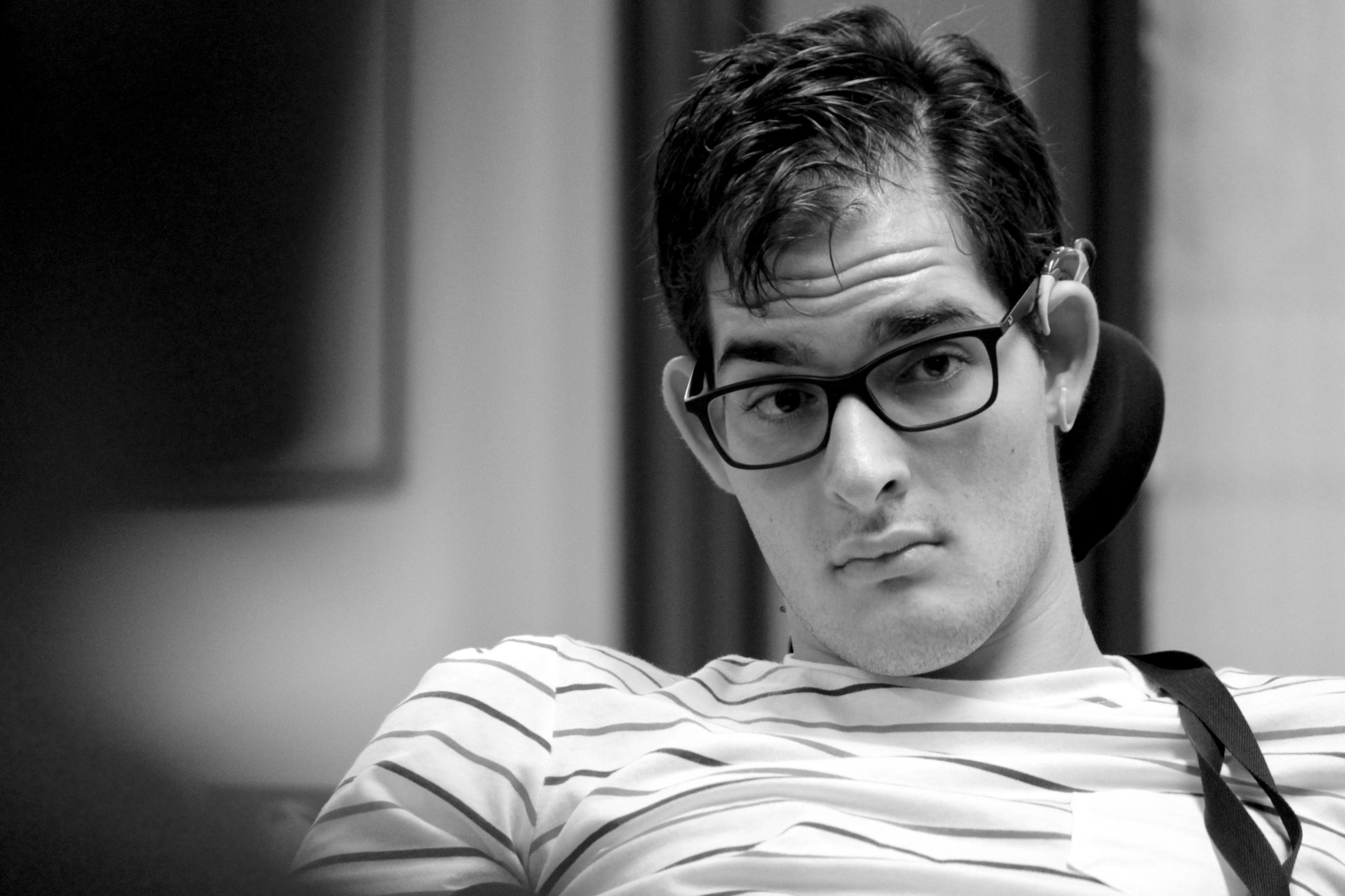 A young man is pictured from the shoulders up. He is leaning back in his chair. He wears thick-rimmed black glasses and although he is clearly listening to someone he is raising his eyebrows with a straight face.