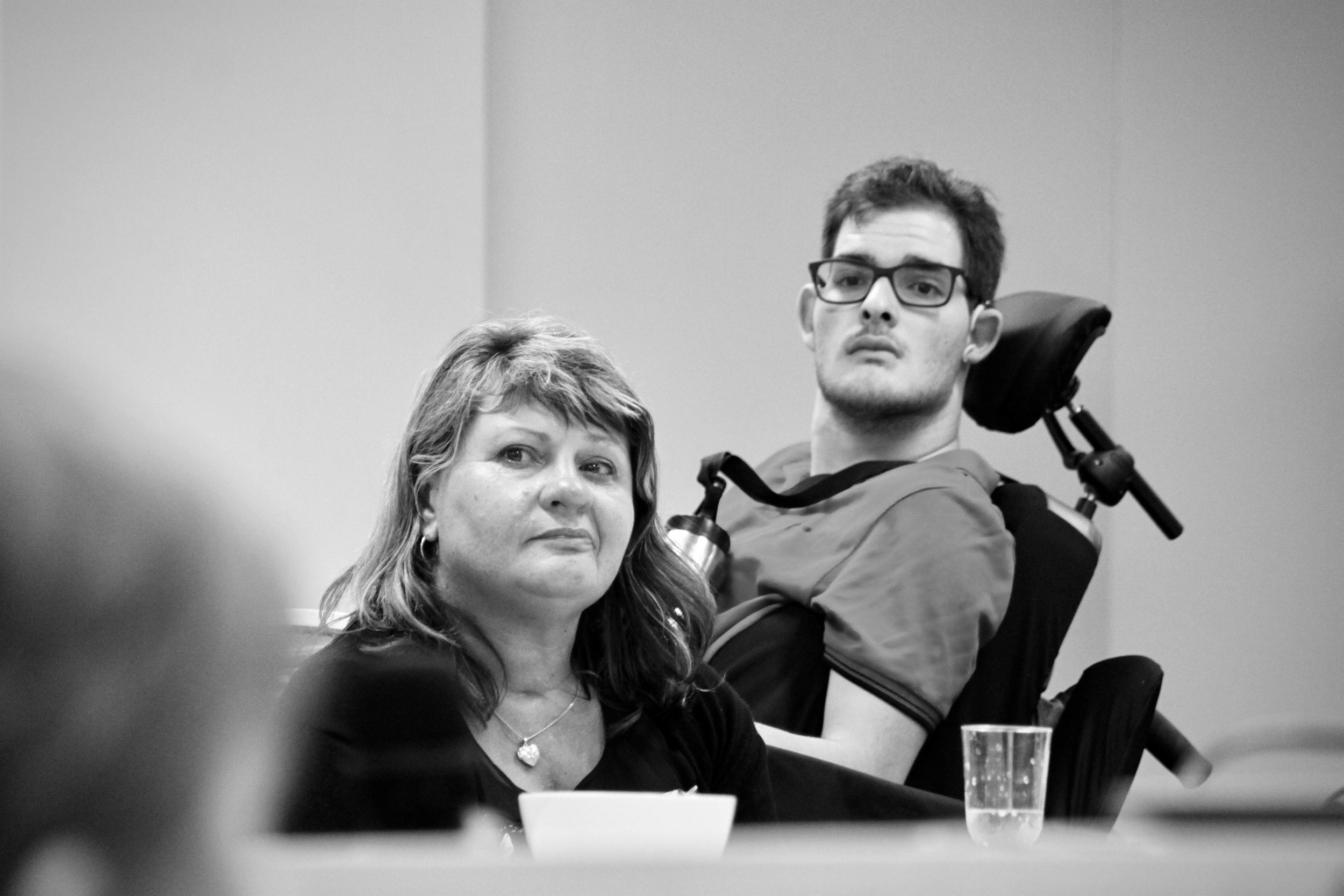 A mature woman and a young man are looking at a speaker out of shot. They are both seated, both with their heads raised up slightly. The young man wears a hearing aid and dark rimmed glasses. The woman's mouth is curled up on one side.