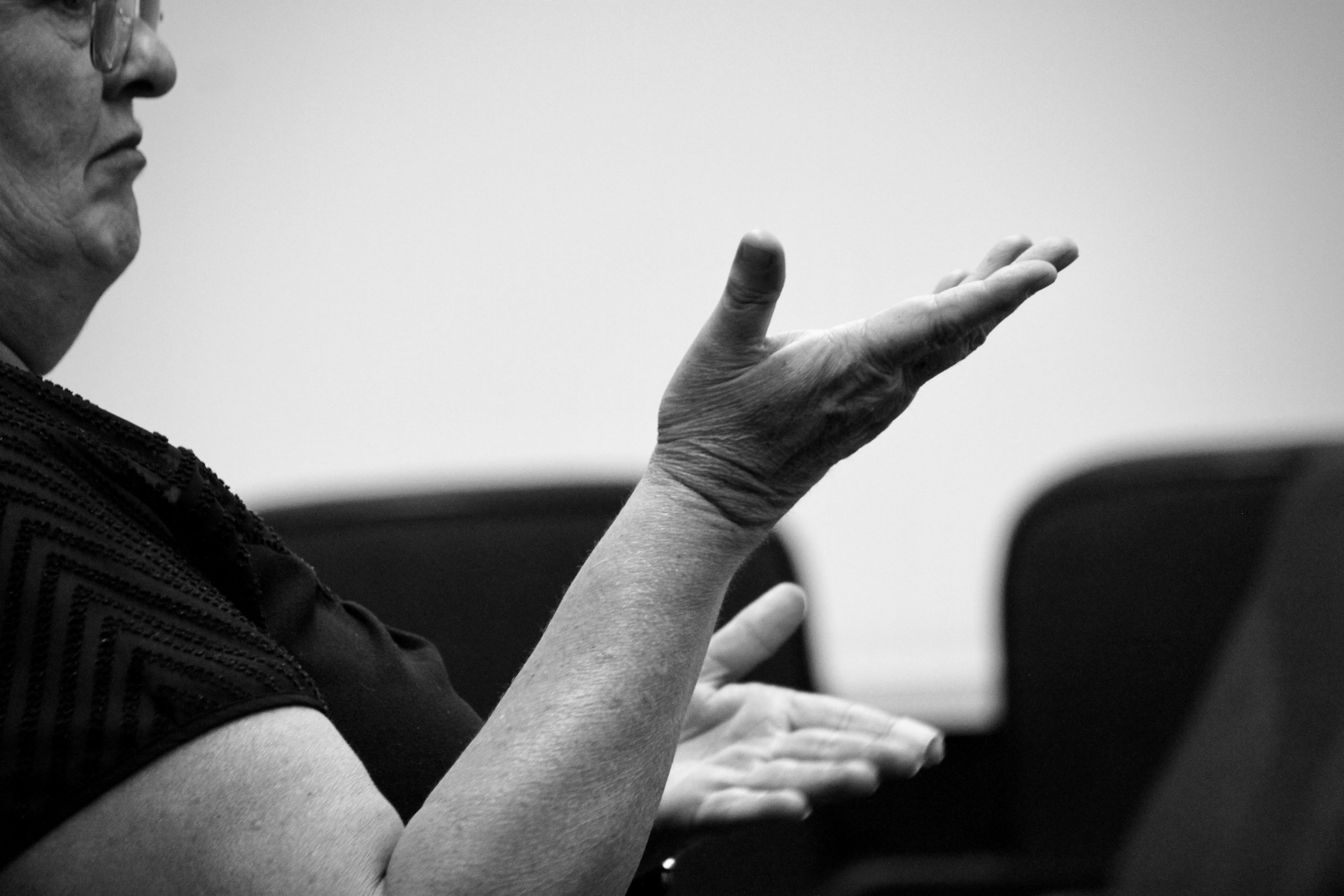 A close up of a woman's arms and hands, she is gesturing with both palms facing up, hands at different heights in front of her. The profile of her face is only just visible on the far left side of the shot.