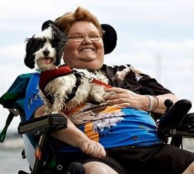 Image description: Tania laughing and holding a dog in her hand.