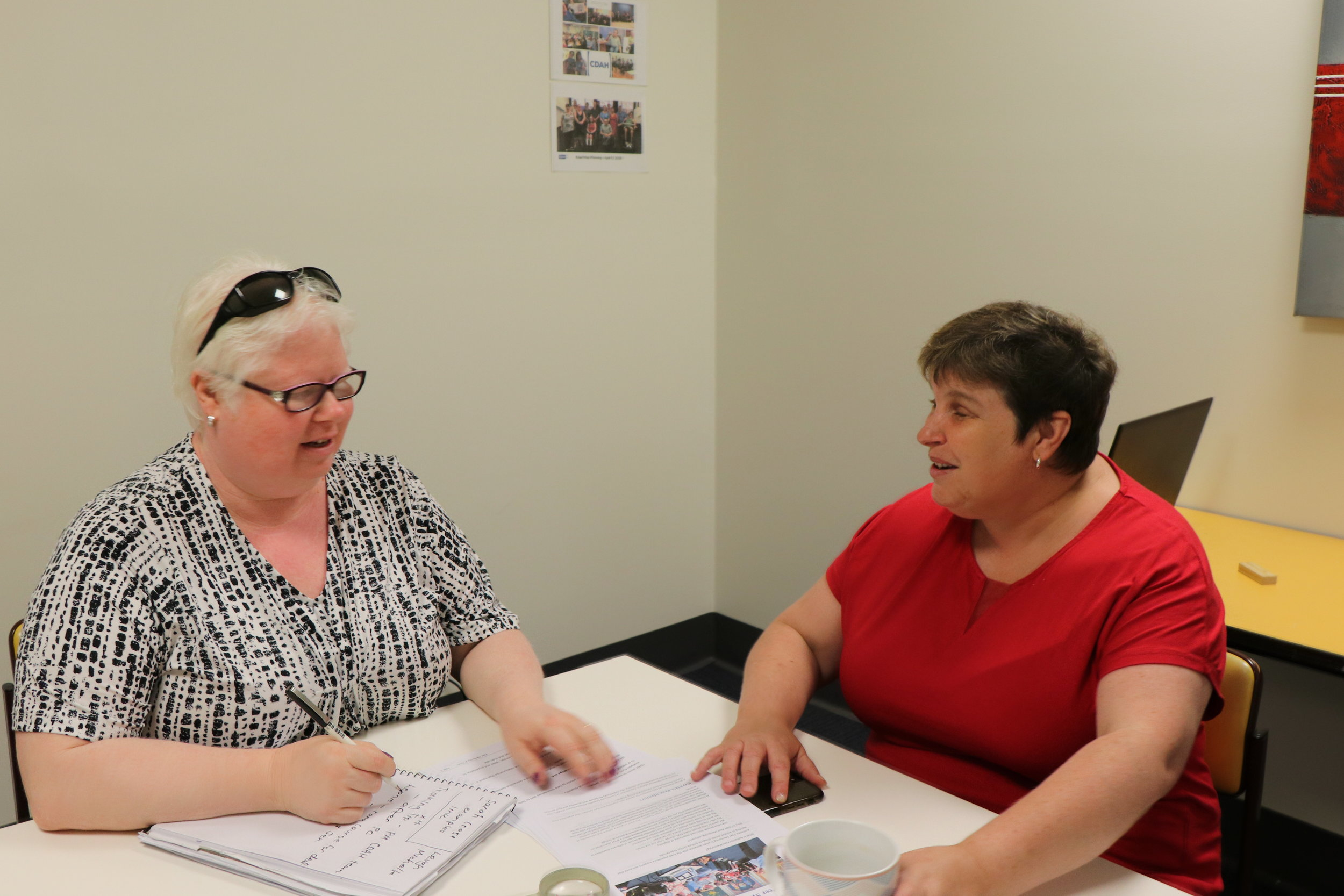 Image description: Photo of Ralene Bock and her colleague Cath Mahony sitting at a table working.
