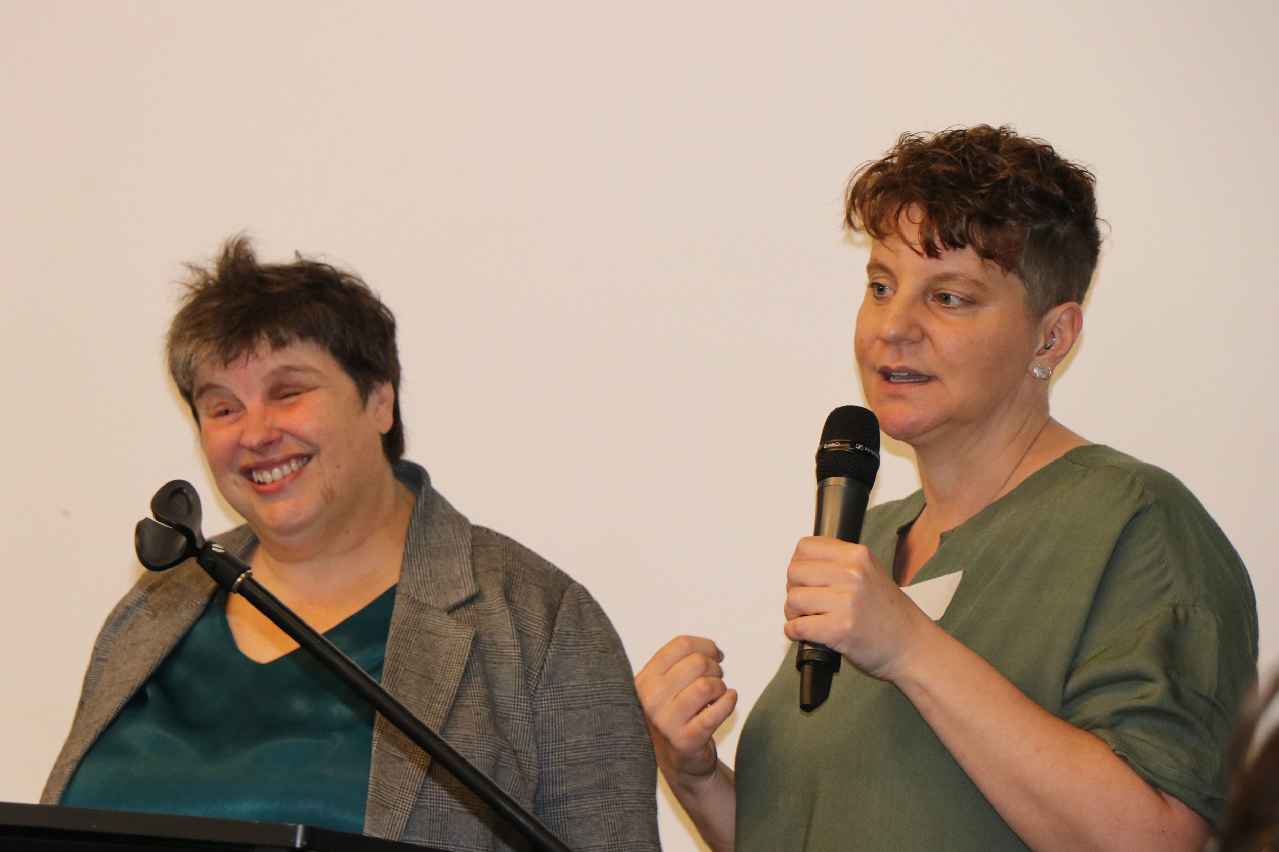 Two women stand at a high desk. One of them holds a microphone and is speaking to the audience (which you can't see in the picture).
