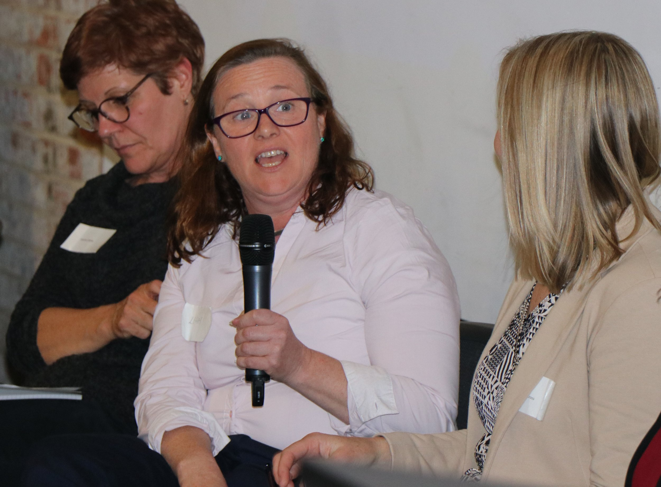 A woman, sitting between two other women, answers a question from the facilitator of a panel discussion.