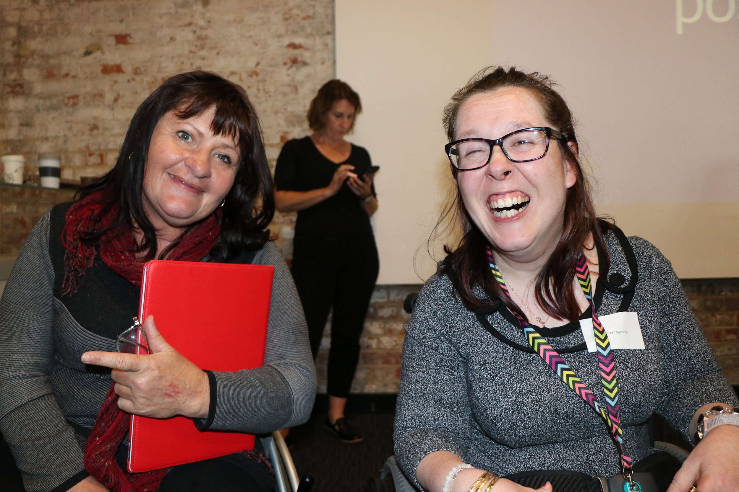 Two women smile broadly at the camera. One of them is holding a red folder in her left arm. Behind them stands another woman who is looking at her smart phone.