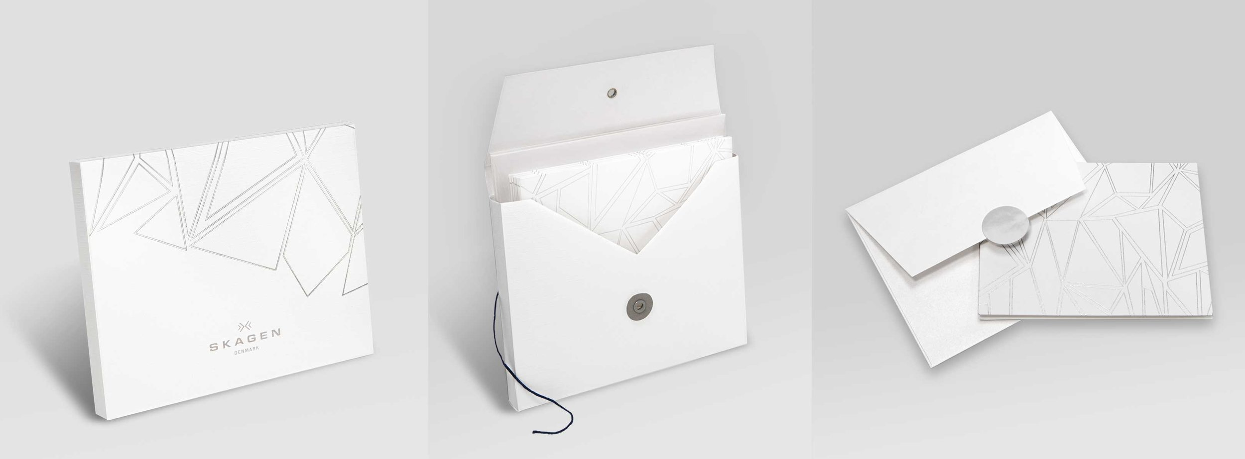 Custom card set design    (concept, mechanicals, sample management through production). Silver foil debossed paper cards and packaging with white shimmery, metallic paper individual envelopes with silver metallic closure stickers.