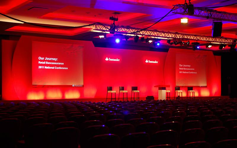 Stock two-screen conference stage set with custom 3D logos and lectern for an event at Westminster Park Plaza, London.