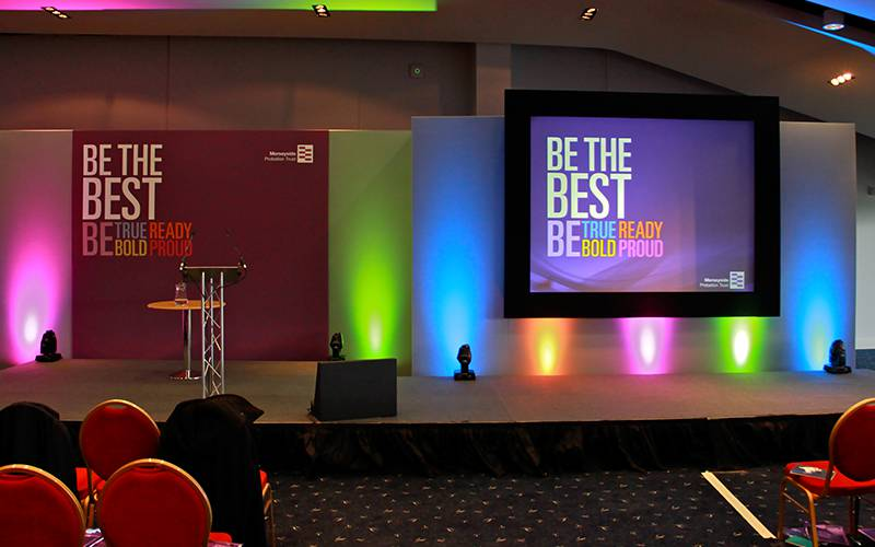 Conference stage set with printed panel, aluminium lectern and single projection screen with uplighting for a conference at Aintree Racecourse in Liverpool.