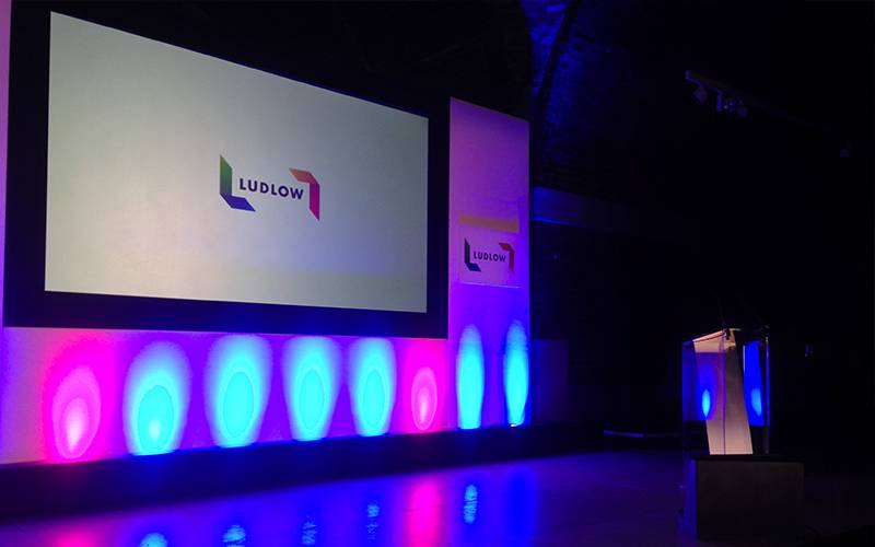 Conference stage set for an event at The Liverpool Metropolitan Cathedral incorporating lighting, branding and an acrylic lectern.