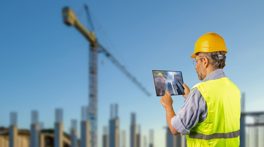 Yellow hard-hatted onstruction worker looking at digital plans.jpg