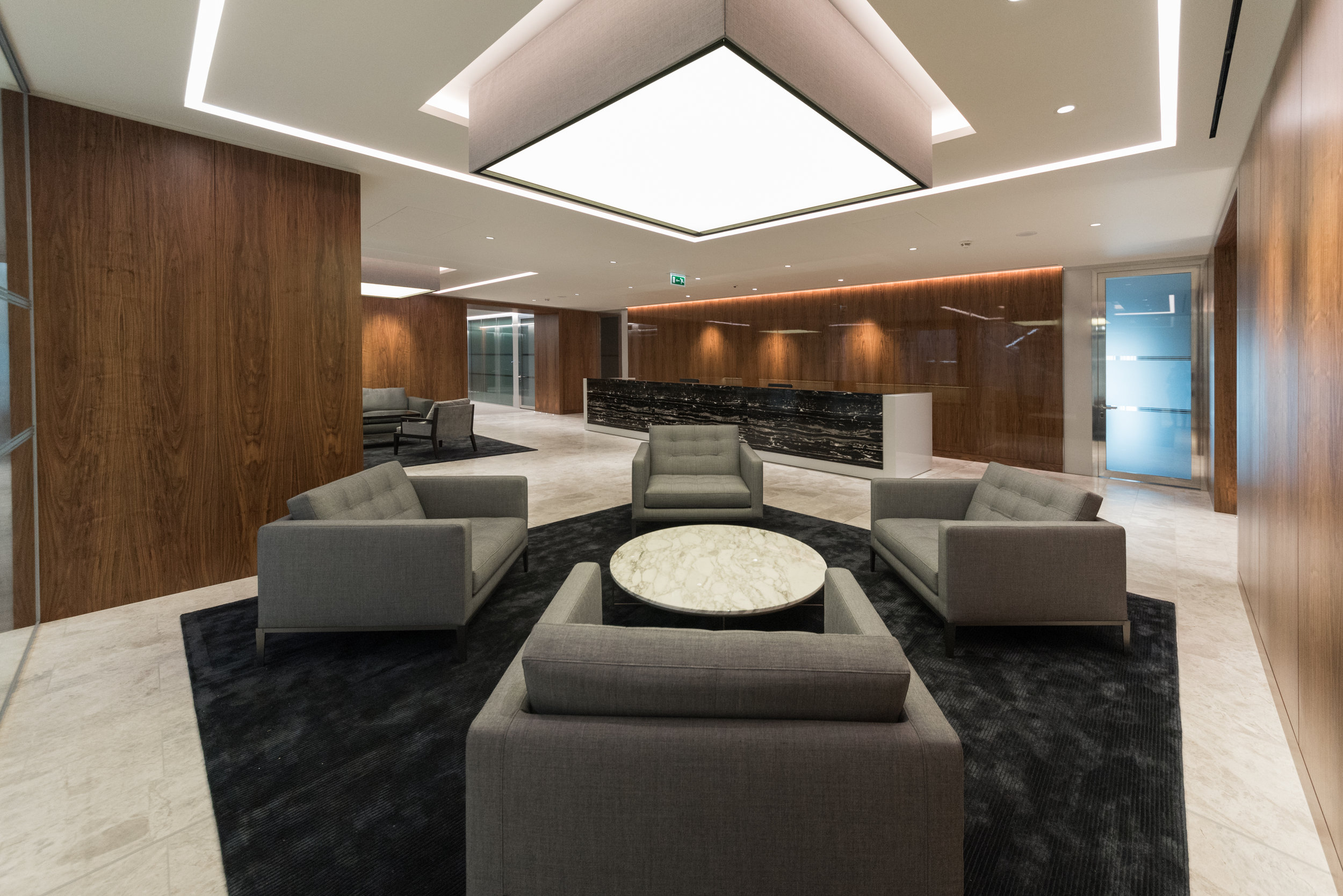 High gloss walnut veneer wall panels and 'silver portoro' stone desk to the main reception area