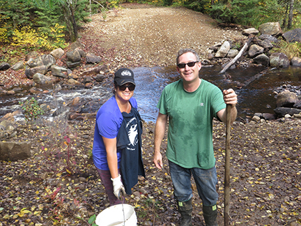 Jen Ashby & Chris Daniels planting shrubs at 10 Mile Creek showing stabilized creek banks as seen in the background with stream flow visible.
