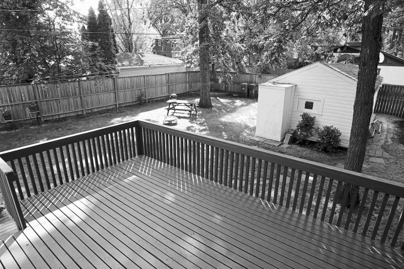 A two-tiered deck overlooks the large yard that is shaded by mature trees.