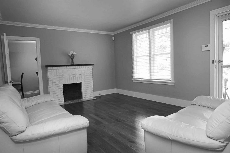 The living room features a wood-burning fireplace with white brick surround, new oak hardwoods and a large window.