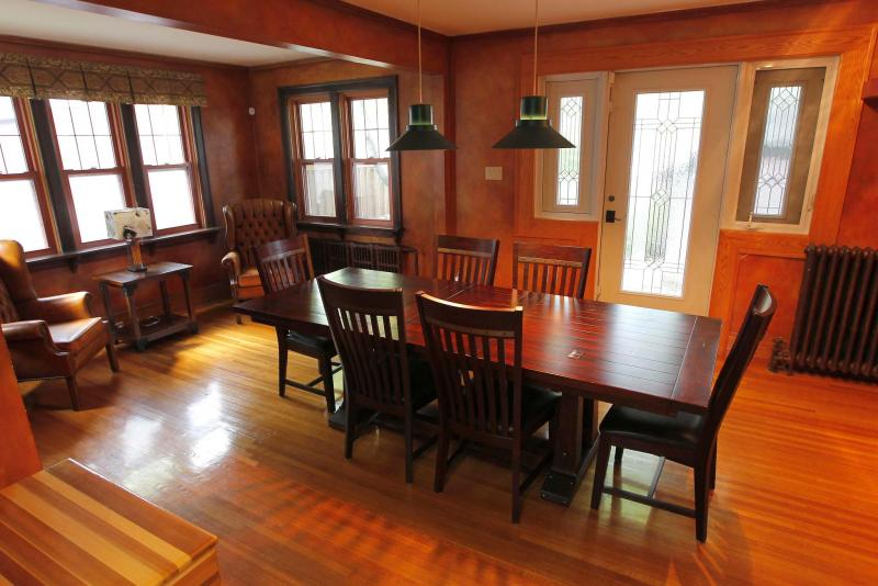 The formal dining room features faux-finished terra cotta walls and is surrounded by five windows.
