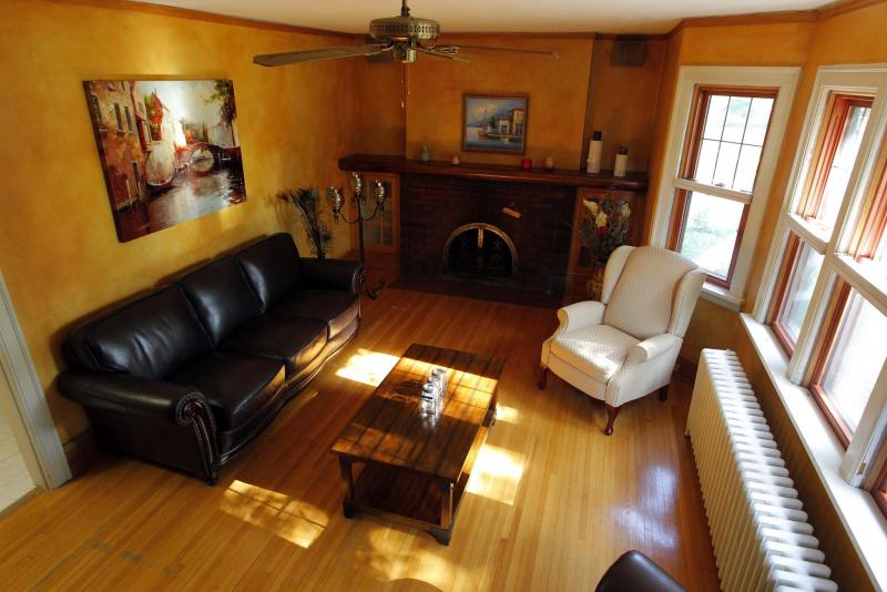 The living room offers a brick fireplace, oak hardwoods and a collection of oversized windows.