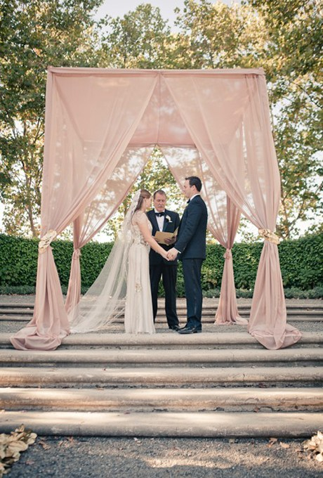 Nothing says the arch, or chuppah, in this case, has to be white. This one is a muted pink, which has found its way into flower palettes in a big way this wedding season. via brides.com, photo Gary Ashley of The Wedding Collective,