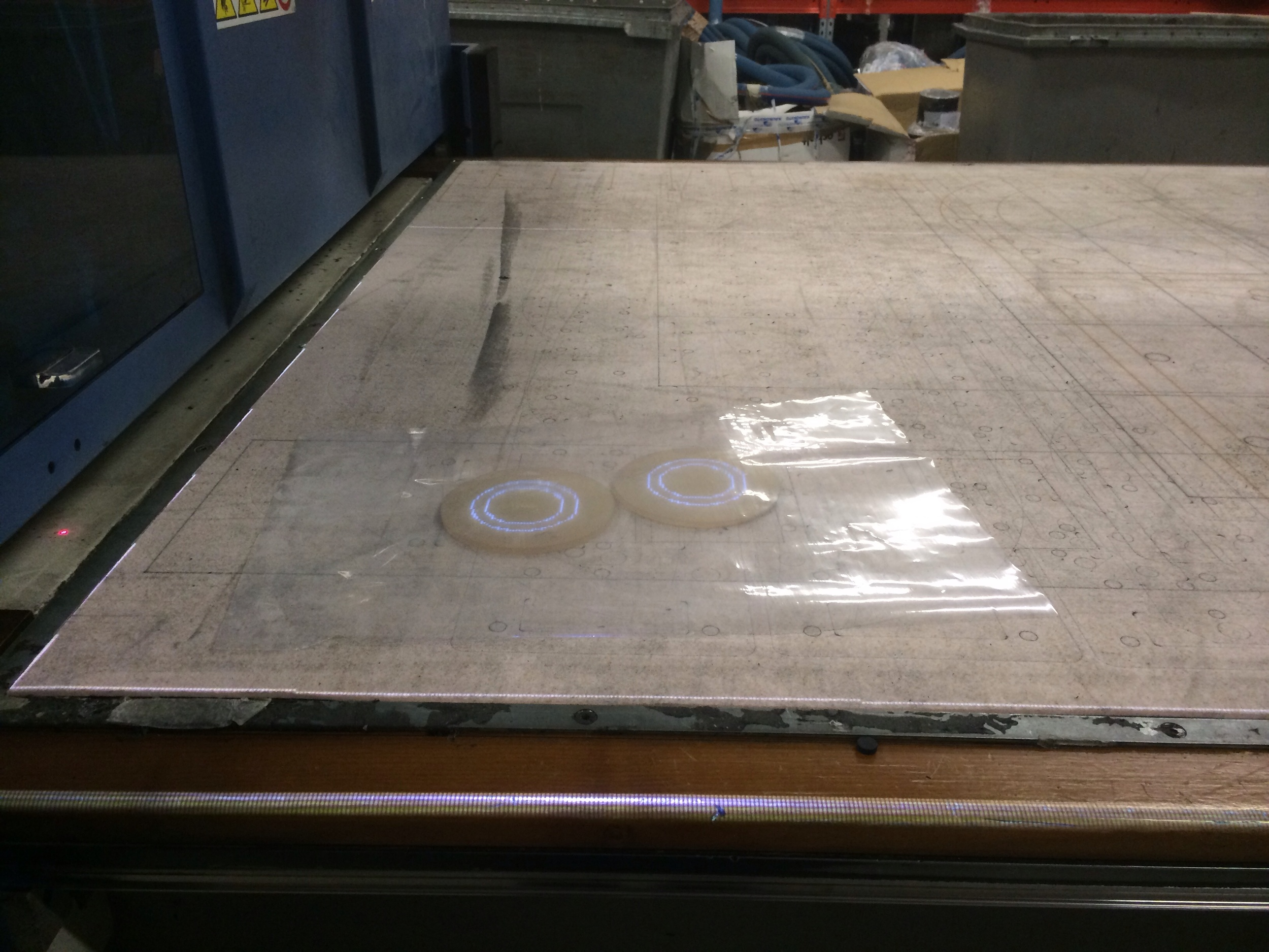 Plastic to increase suction on the vacuum table below to hold the flanges in place while cutting.